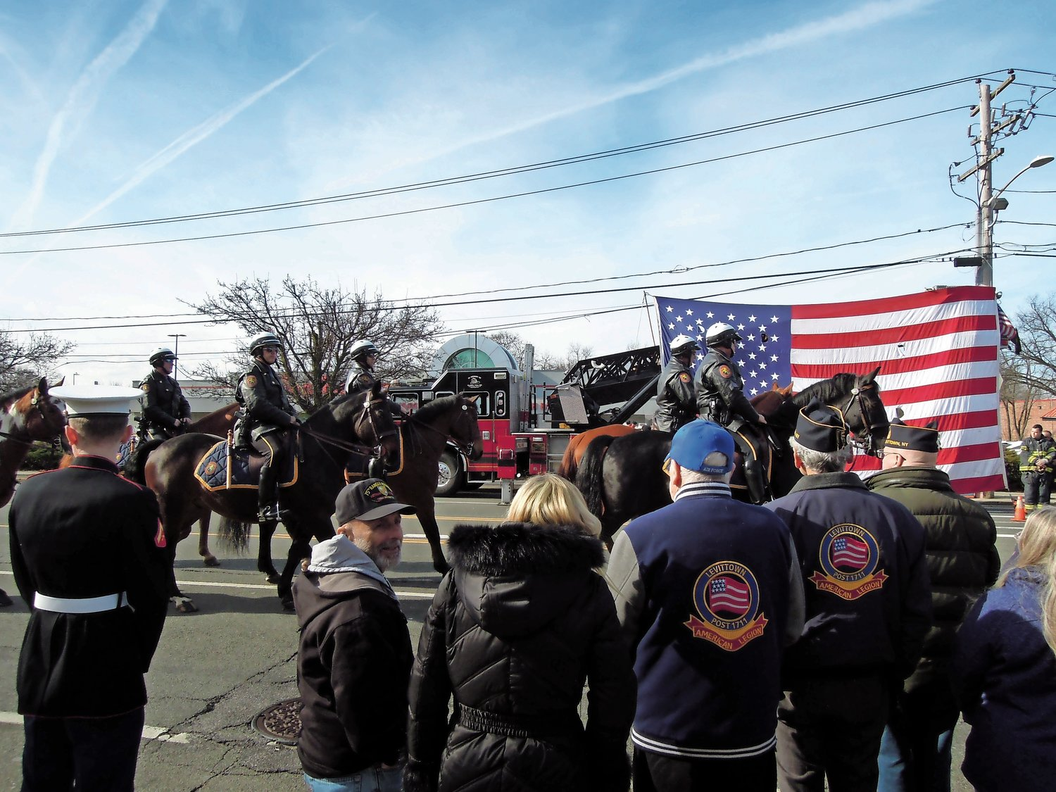 The Nassau County Police Department's mounted unit paid its respects in front of an oversized American flag, courtesy of the Wantagh Volunteer Fire Department.