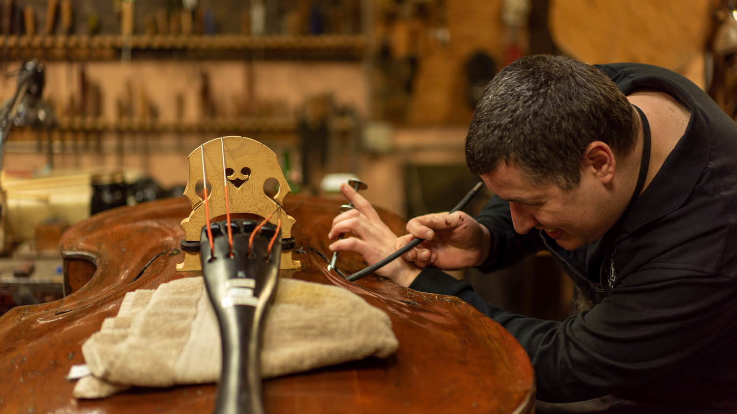 Kris Fleischmann worked on an instrument in one of the back rooms of the Samuel Kolstein Violin Shop after a Feb. 4 grand reopening ribbon-cutting ceremony, which celebrated longtime owner Barrie Kolstein passing his duties to Manny Alvarez.