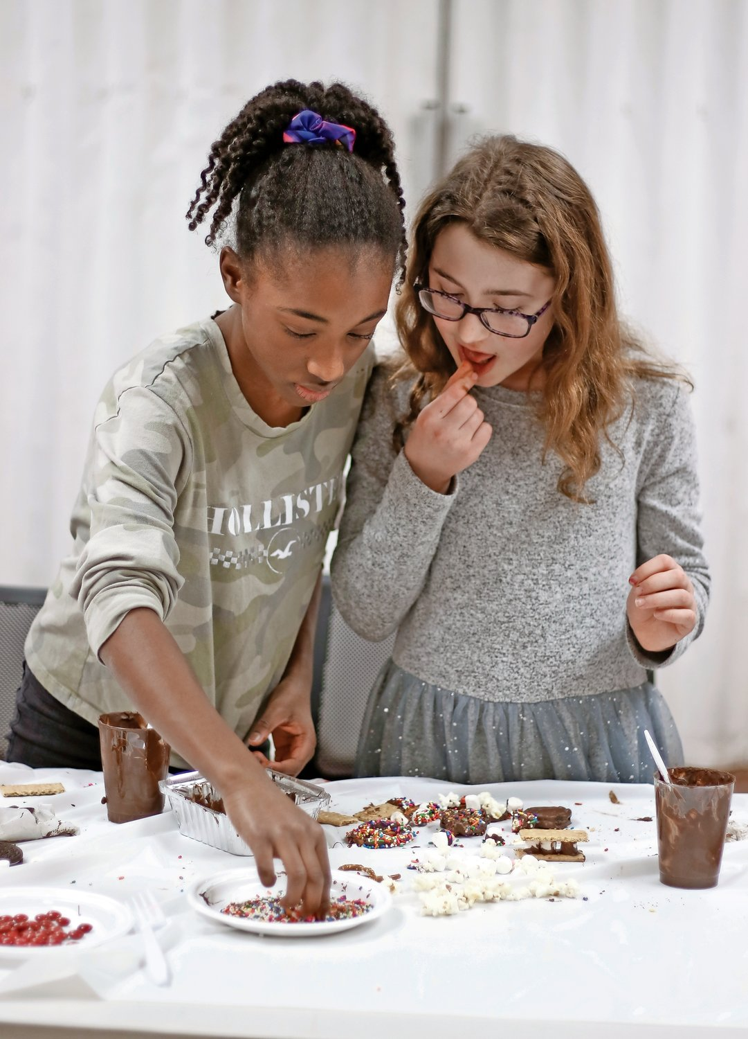 Aspiring pastry chefs Clairevy Maingrette, 12, left, and Claire Arnoff, 11, practiced their chocolate-making skills at the Bellmore Memorial Library on Feb. 3. There they created heart-shaped lollipops to give to their family and friends for Valentine's Day.