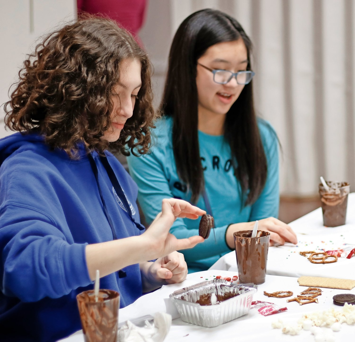 Ruby Mattes, front, and Elle Soontarodom, both 14, dipped Oreos, pretzels and popcorn into melted chocolate during the class.