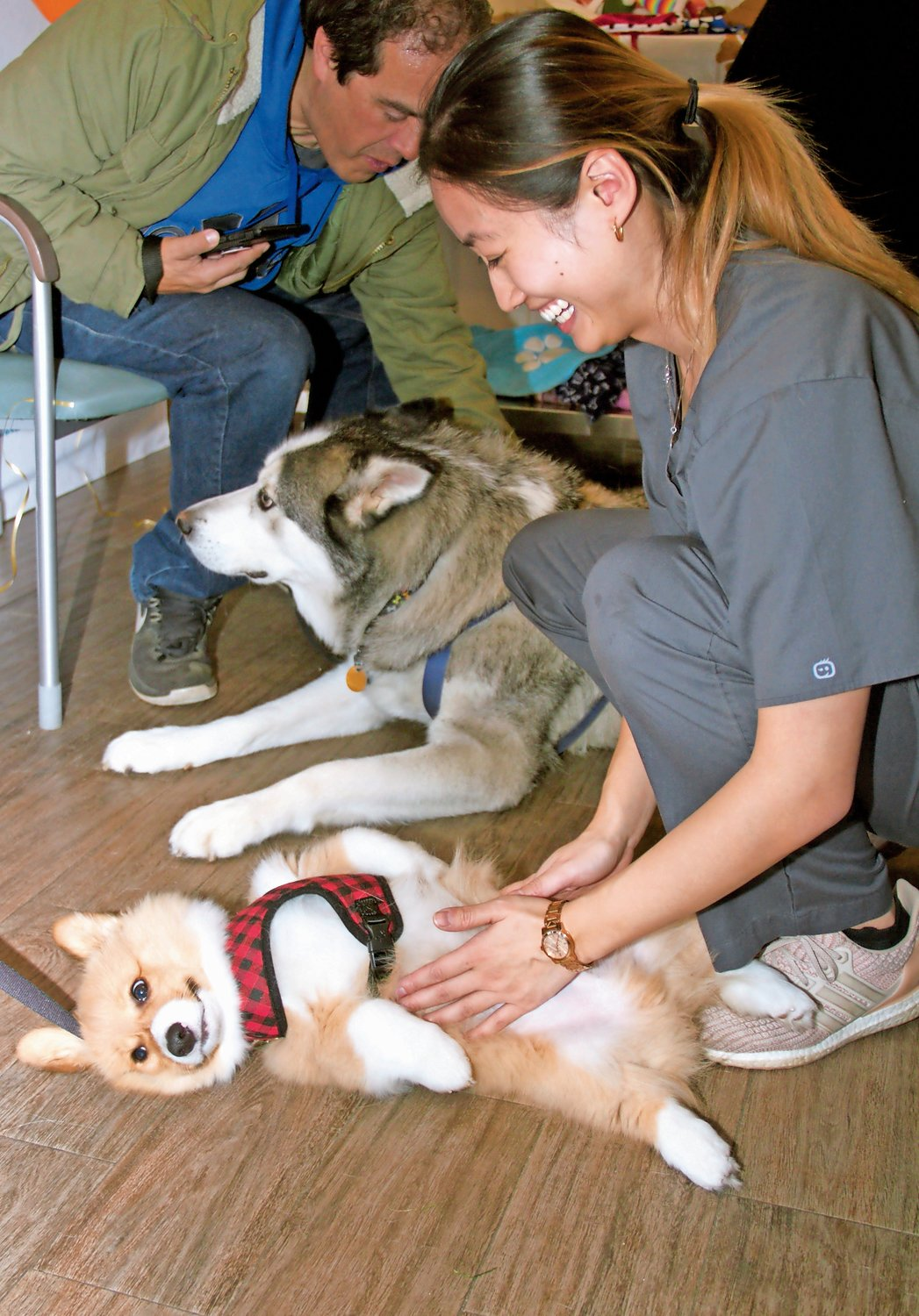 Veterinary Care Group's Dr. Jamie Zhen, left, gave some love to a corgi named Kobe.
