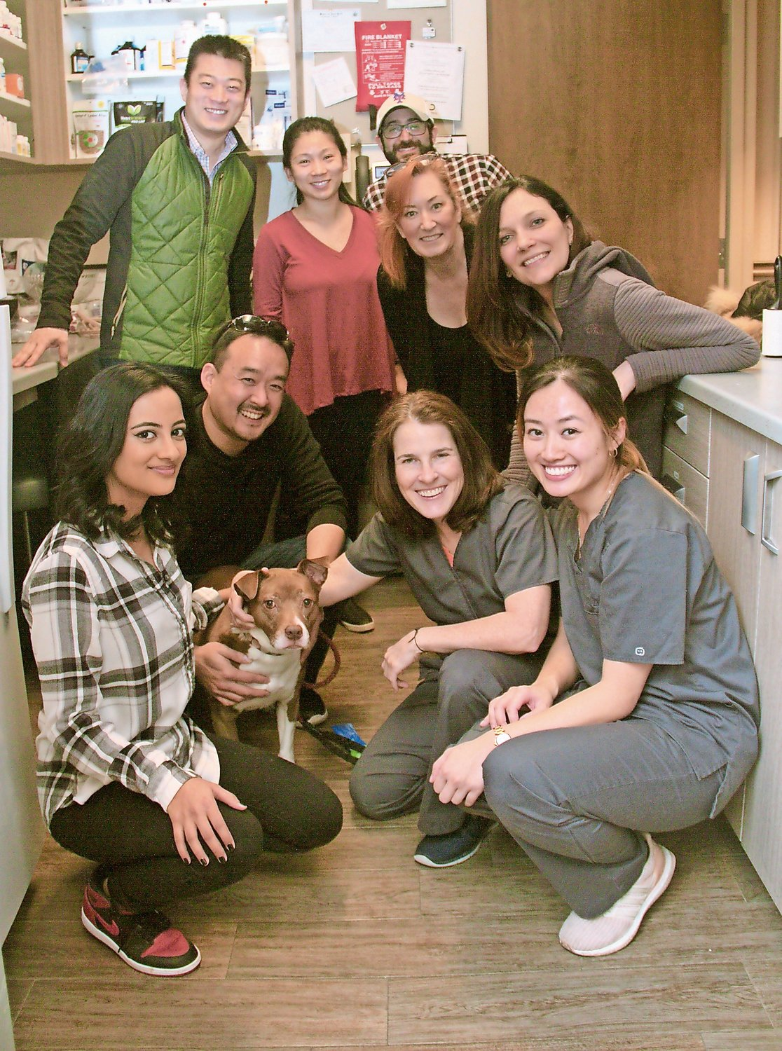 The staff at the Veterinary Care Group posed with a pit bull mix at the Pupperazzi Pawty.
