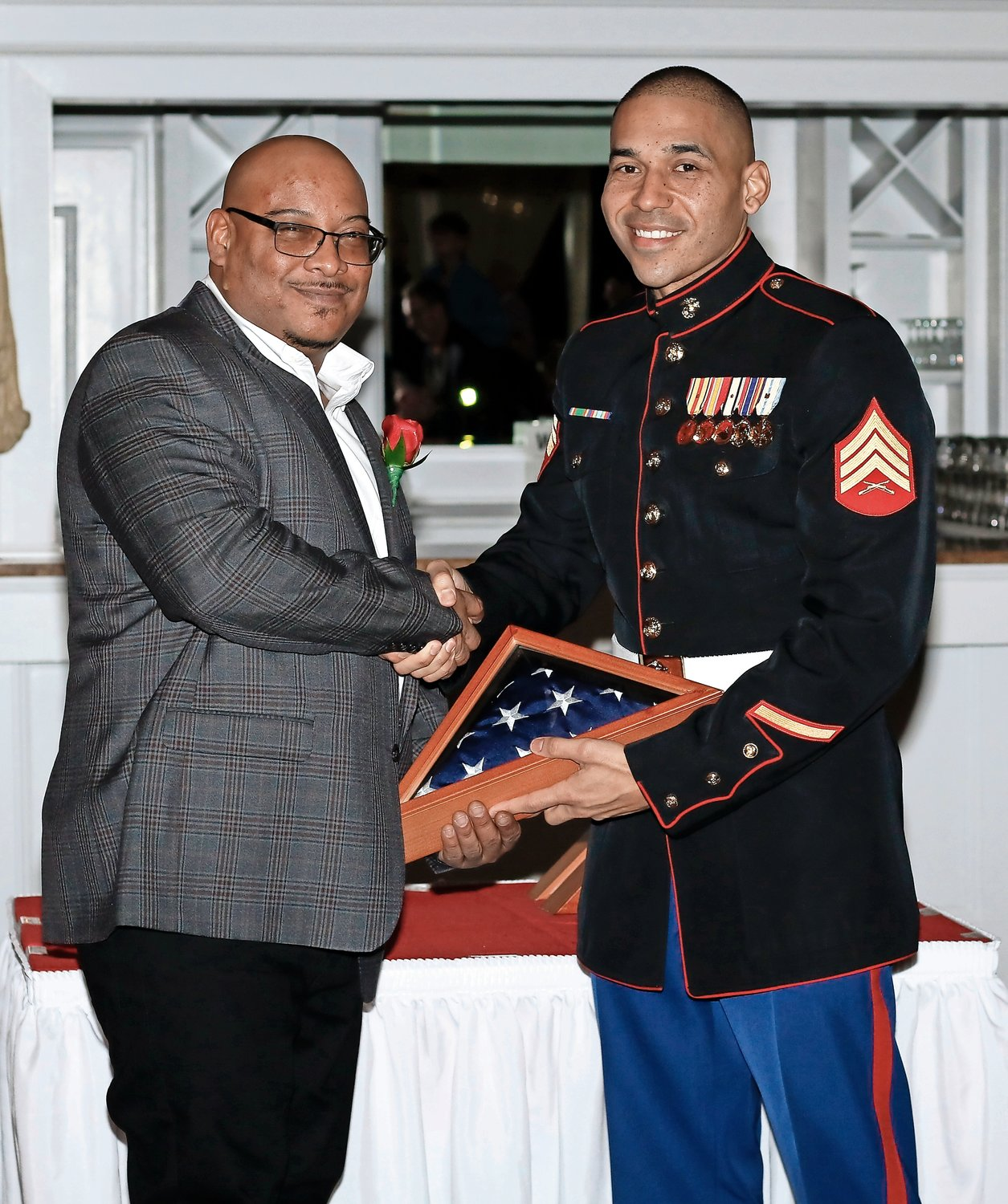Active duty Marine Sgt. Jason Hanna, right, presented Lance Cpl. Jason Rogers and three other honored veterans with American flags at the Island Park Civic Association's annual Love Your Troops event on Feb. 8.