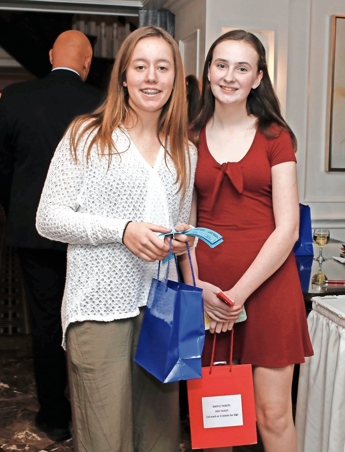 Volunteers Gabby Hohmann, left, and Katelyn Doyle helped sell a variety of raffles and 50/50 tickets at the dinner.