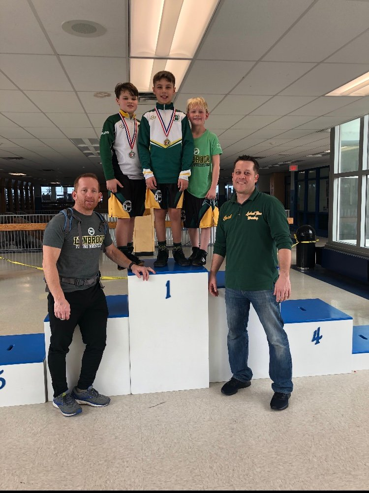 Members of the Lynbrook Titans Wrestling Program have found plenty of success this season. Brendan Barkley, second from left, Bryce Boccio and Tristan Hollenstein have received guidance from coaches Doug Stern, far left, and Mat Hollenstein.
