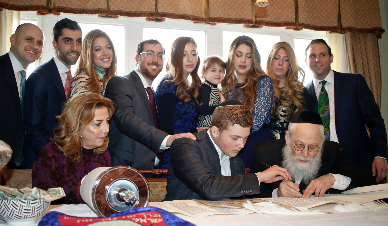 The Fried family gathered at the table as Rabbi Moshe Klein added the final letters to the torah. He was Joined at the table by Avi Fried, 15, center, and his mother Osmat, left.