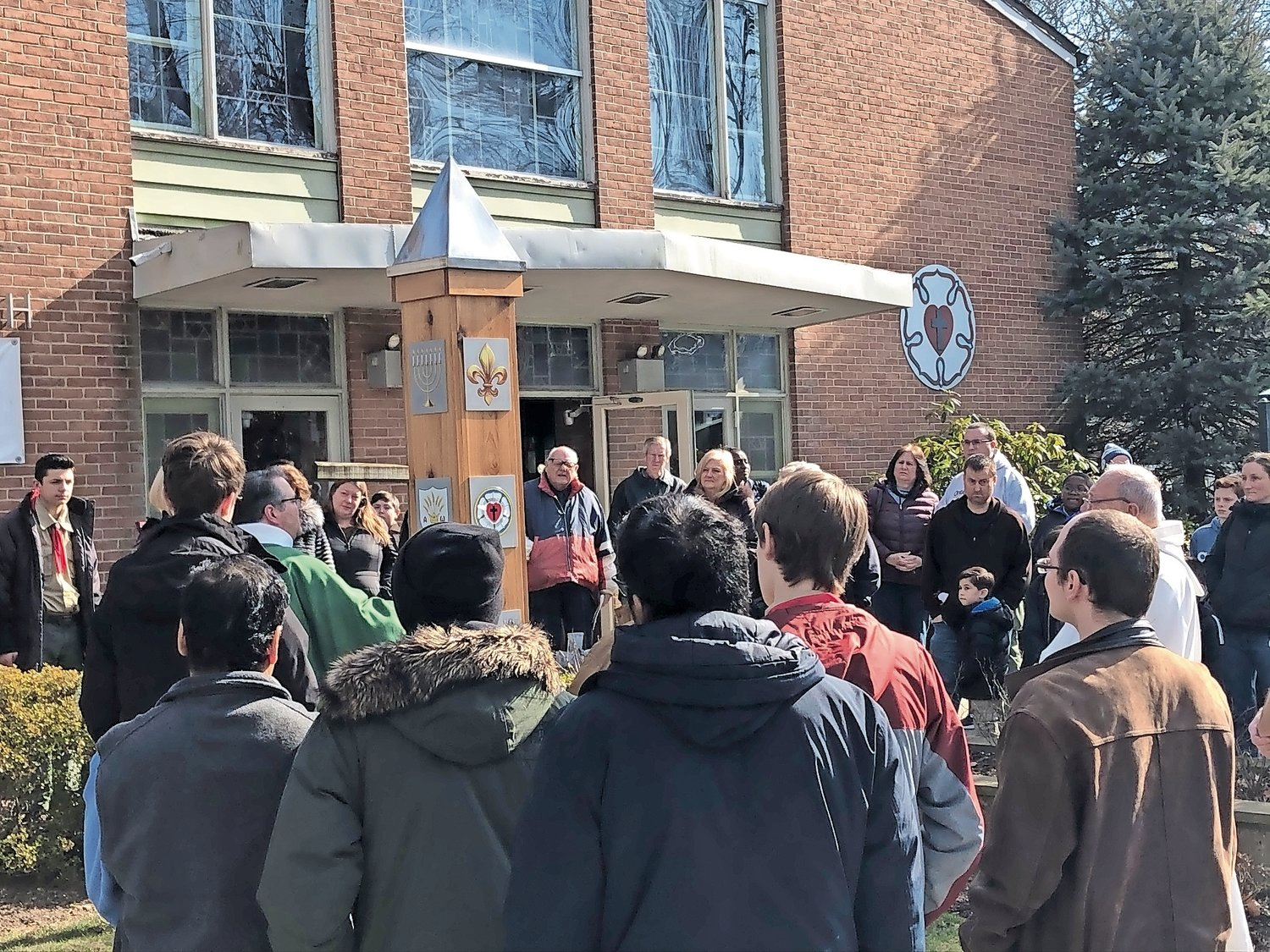 Congregants of St. John's Lutheran Church in Merrick gathered after Mass on Feb. 9, right, as Kirschbaum anointed the newly erected peace pole there. Boy Scout Erik Conlon, of Merrick, organized the project.