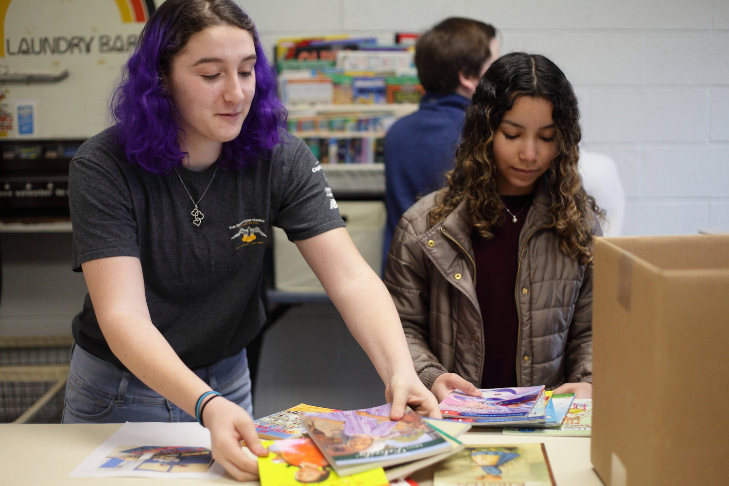 Carly Wolfe, 14, far left, and Bela Castellanos, 13, found books they enjoyed reading when they were children among those that were brought to the laundromat.