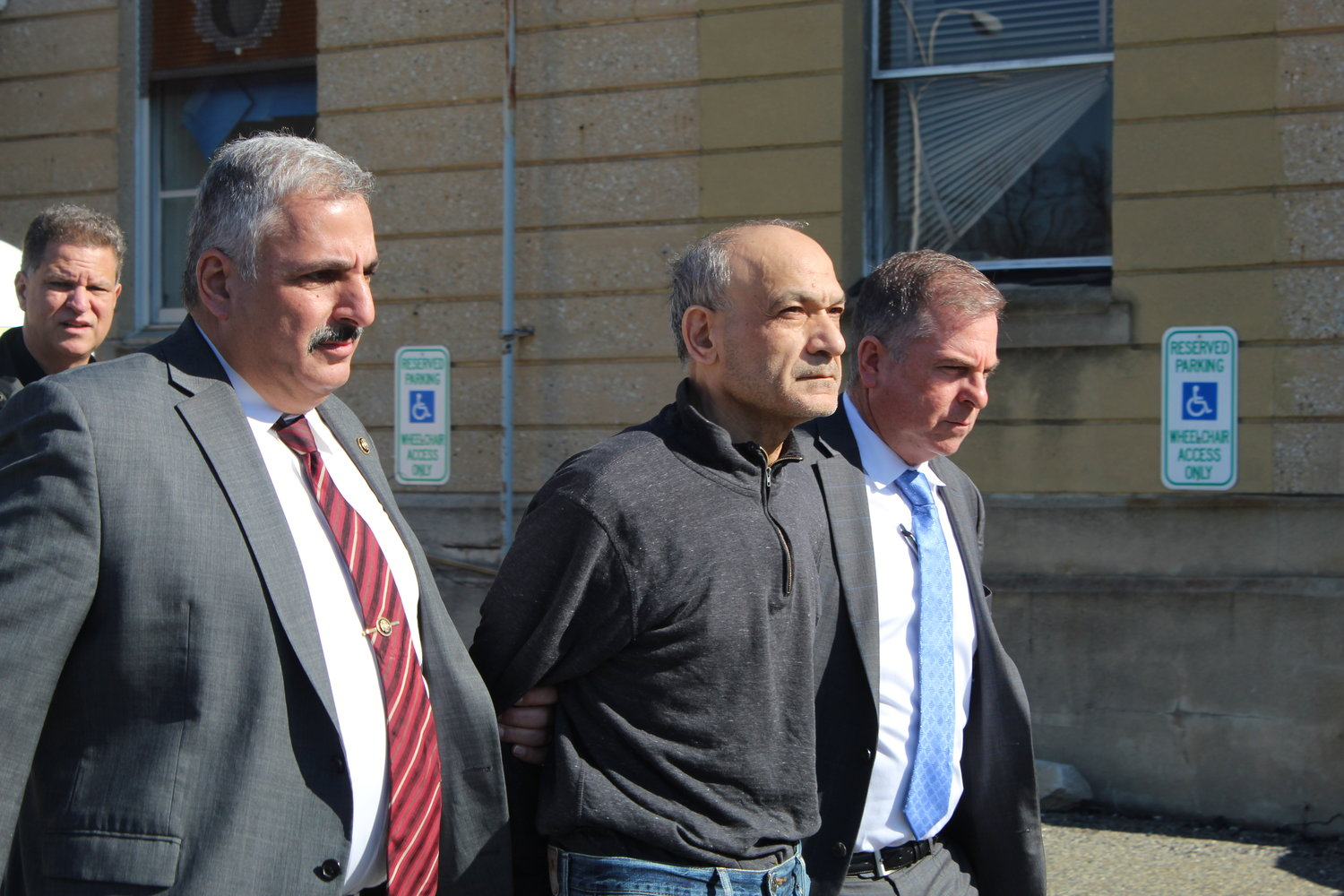 Detectives escorted John Gerges, center, of Merrick, from the detention facility at Nassau County Police Headquarters Monday morning. Gerges was arrested for allegedly strangling his wife, Marvat Gerges, to death in their home at 14 Lindgren St.
