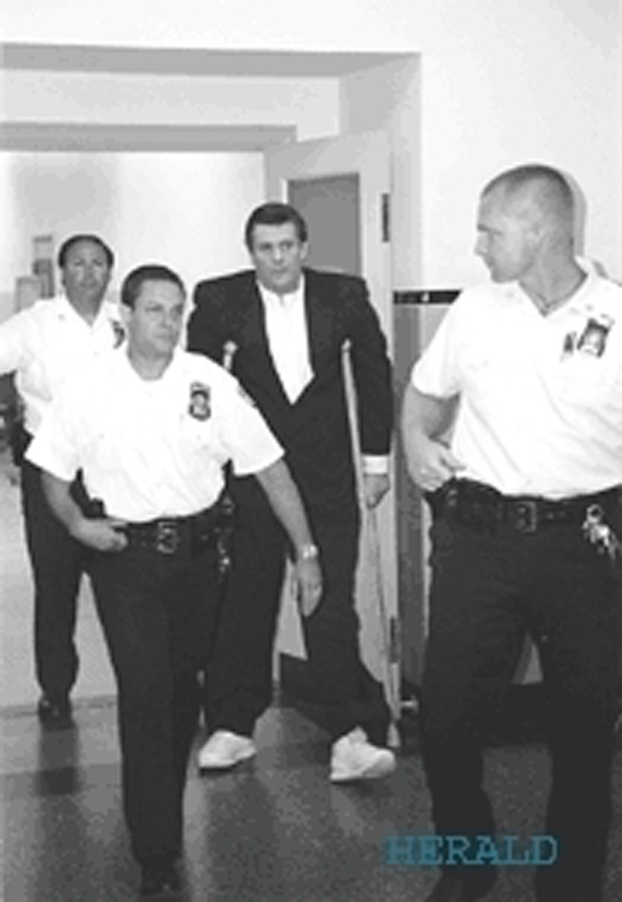 John Pierotti, in crutches, being escorted to court in 2000.