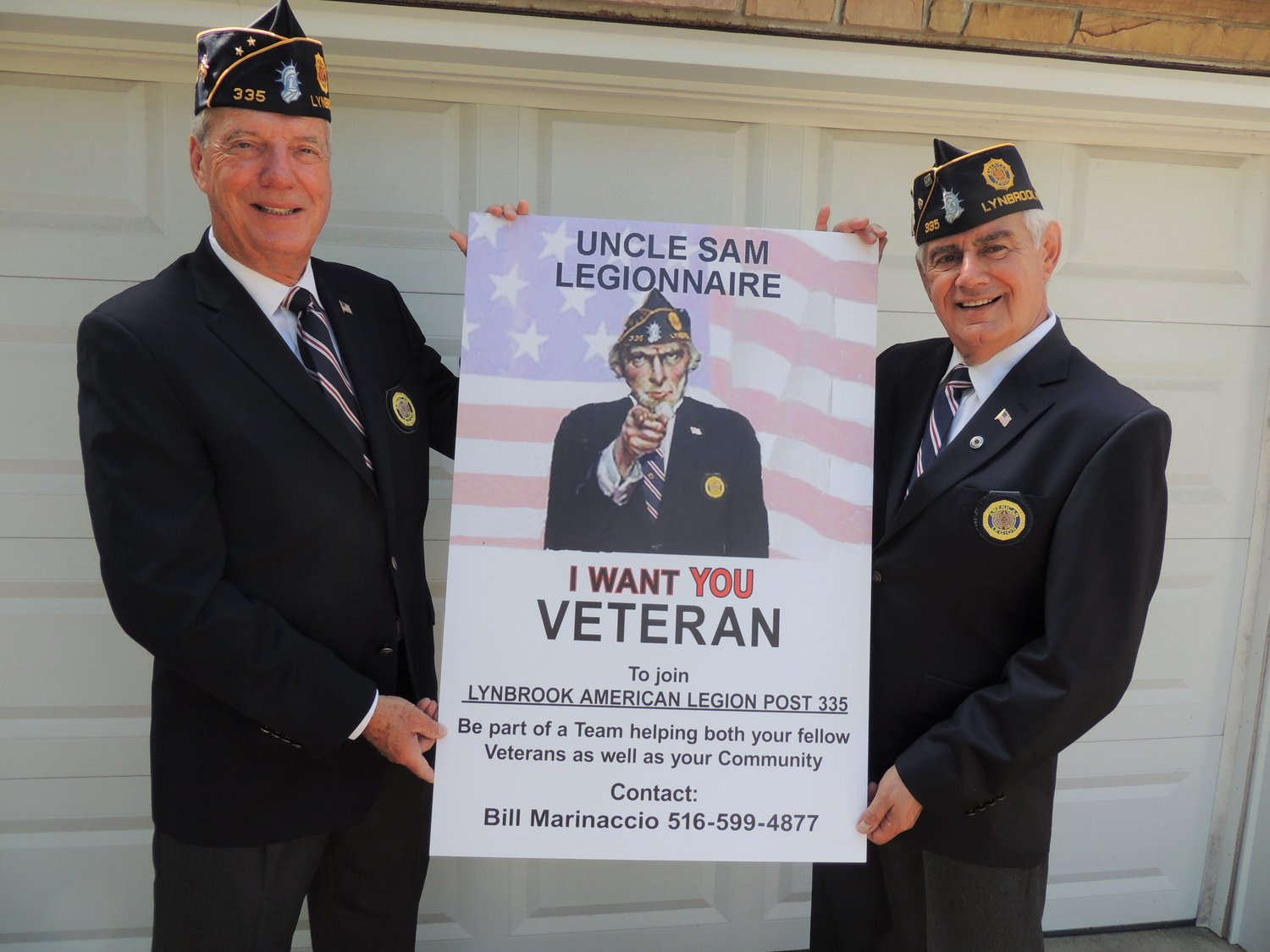 Lynbrook will host a small Veterans Day drive-by parade on Monday. Above, American Legion Post 335 members Steve Grogan, left, and Bill Marinaccio with their member recruitment poster.