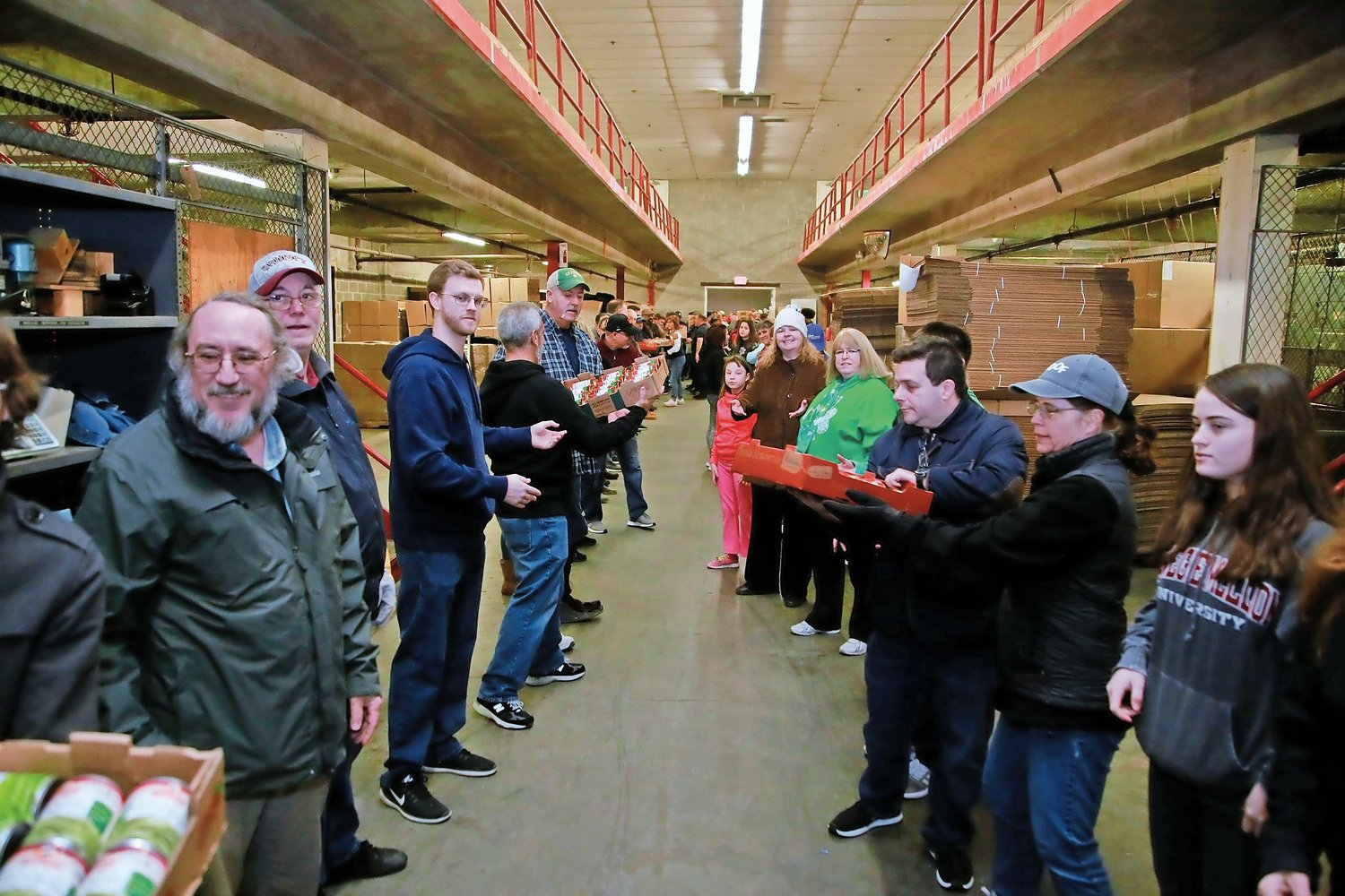 Volunteers formed an assembly line at the Long Island Council of Churches' food pantry in Freeport last year. Rob and Mary Hallam hope to deliver donations to the LICC on April 25.