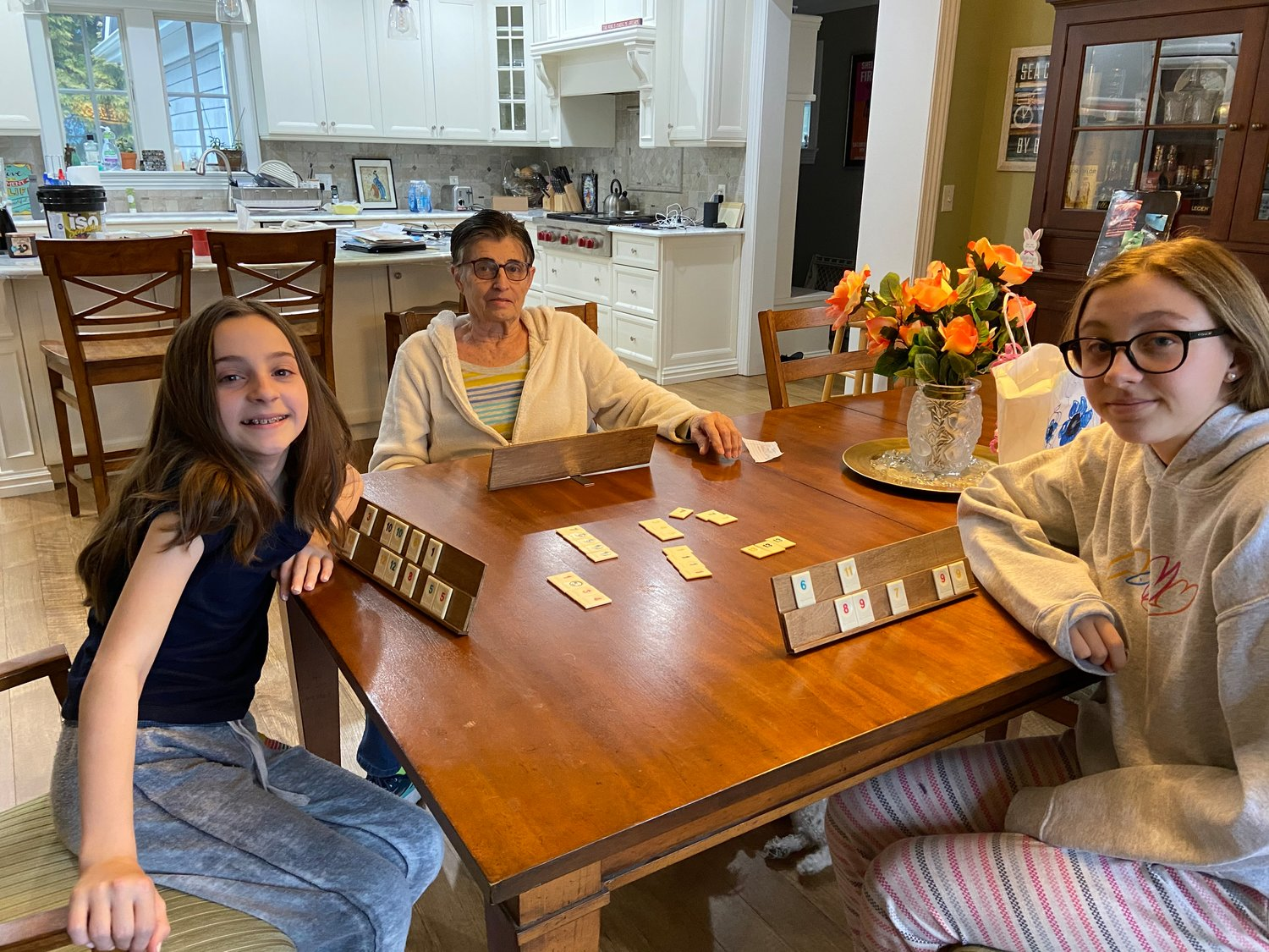 Barbara Lillis, center, has spent much of her time at home playing games like Rummikub with her granddaughters Jordan, left, and Jessica.