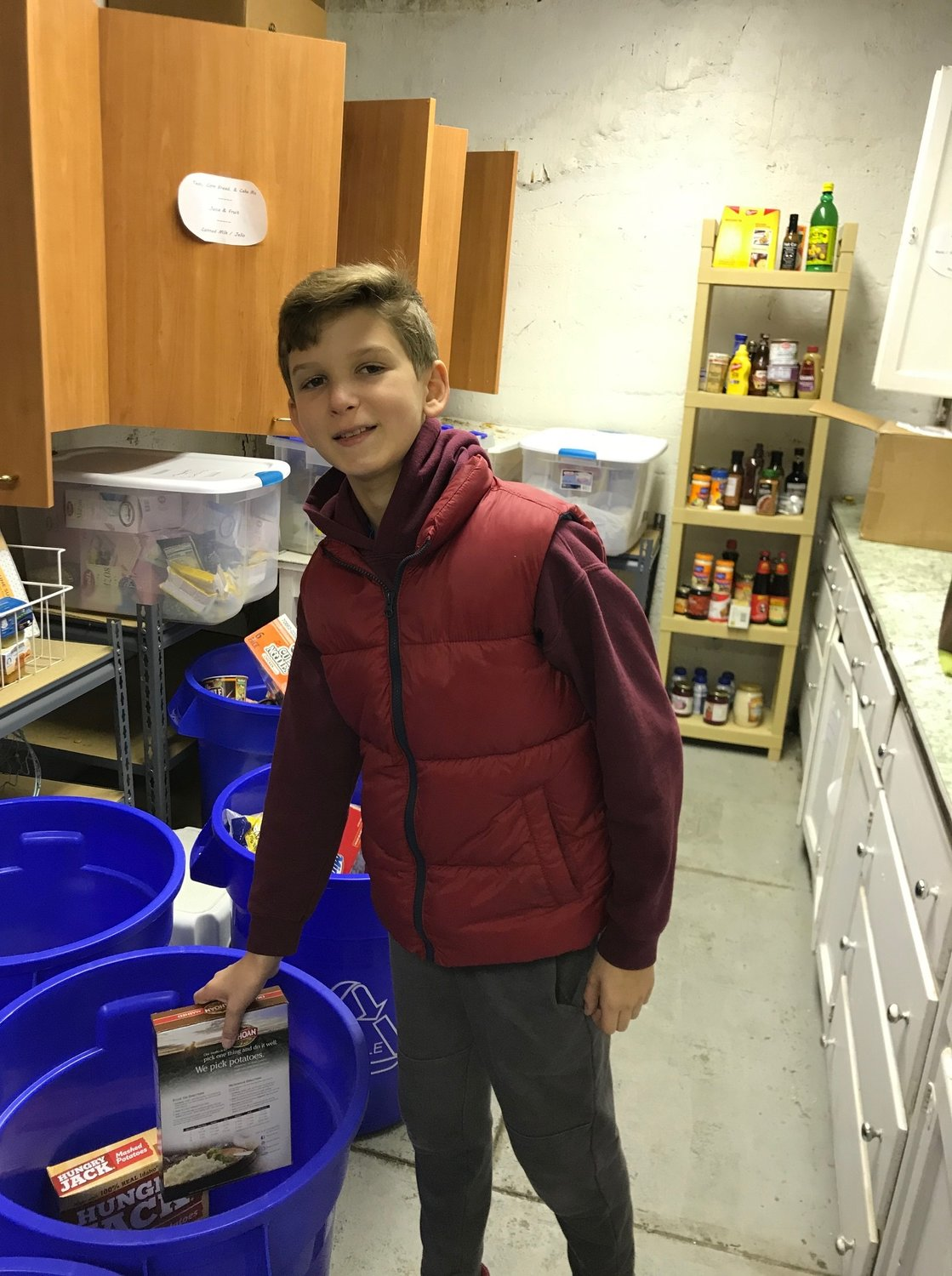 Gregory Nemirov, 12, is taking the time to help Sea Cliff's Mutual Concern Committee stock its food pantry for seniors in need.C