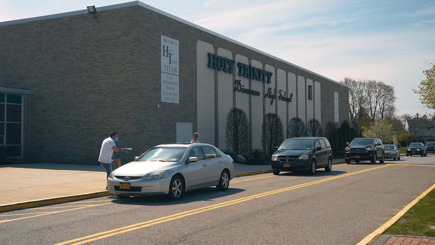 Cars lined up outside Holy Trinity Diocesan High School, in Hicksville, on Easter, where Edward and Jessica Dennehy, of Mad Men Bespoke Barbershop, gave out packages of masks.