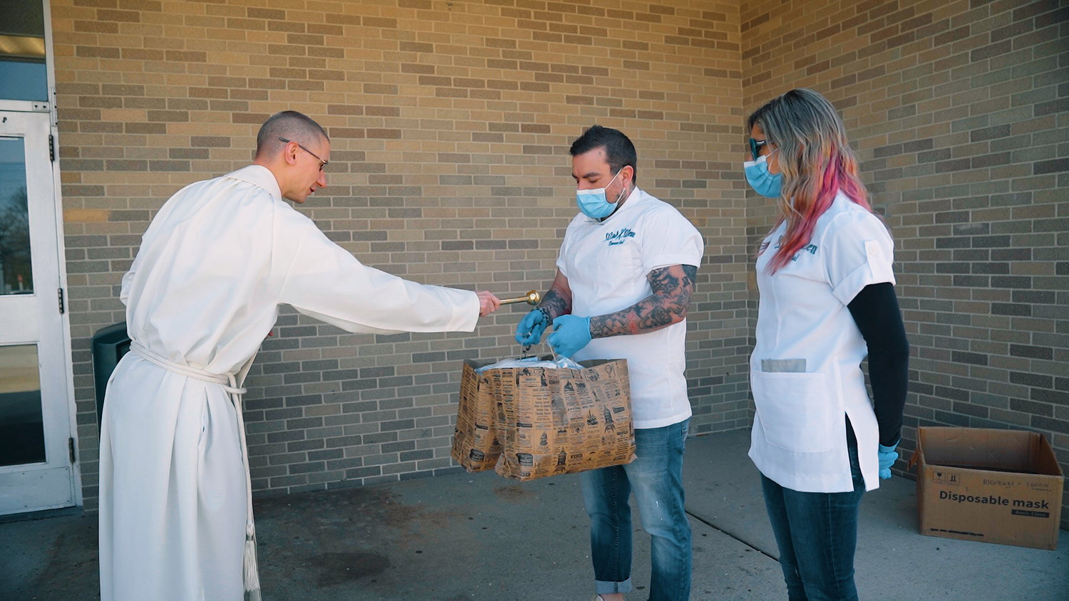 Rev. Liam McDonald blesses the masks and the couple. who gave out about 1,000 masks in honor of Easter; it was the second distribution, and the couple says more are to follow.