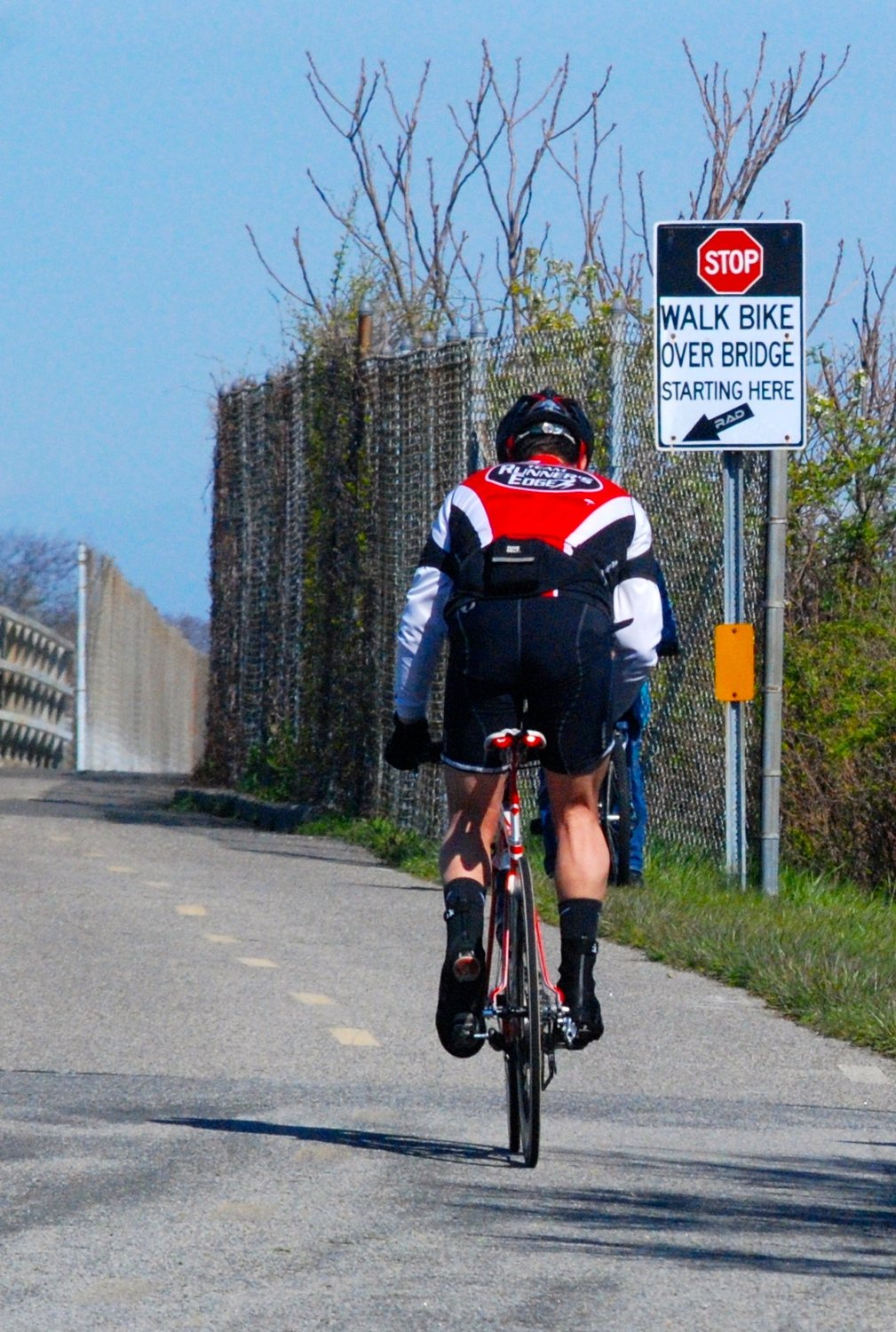 A cyclist cresting a hill on the path from Jones Beach back to Cedar Creek Park.
