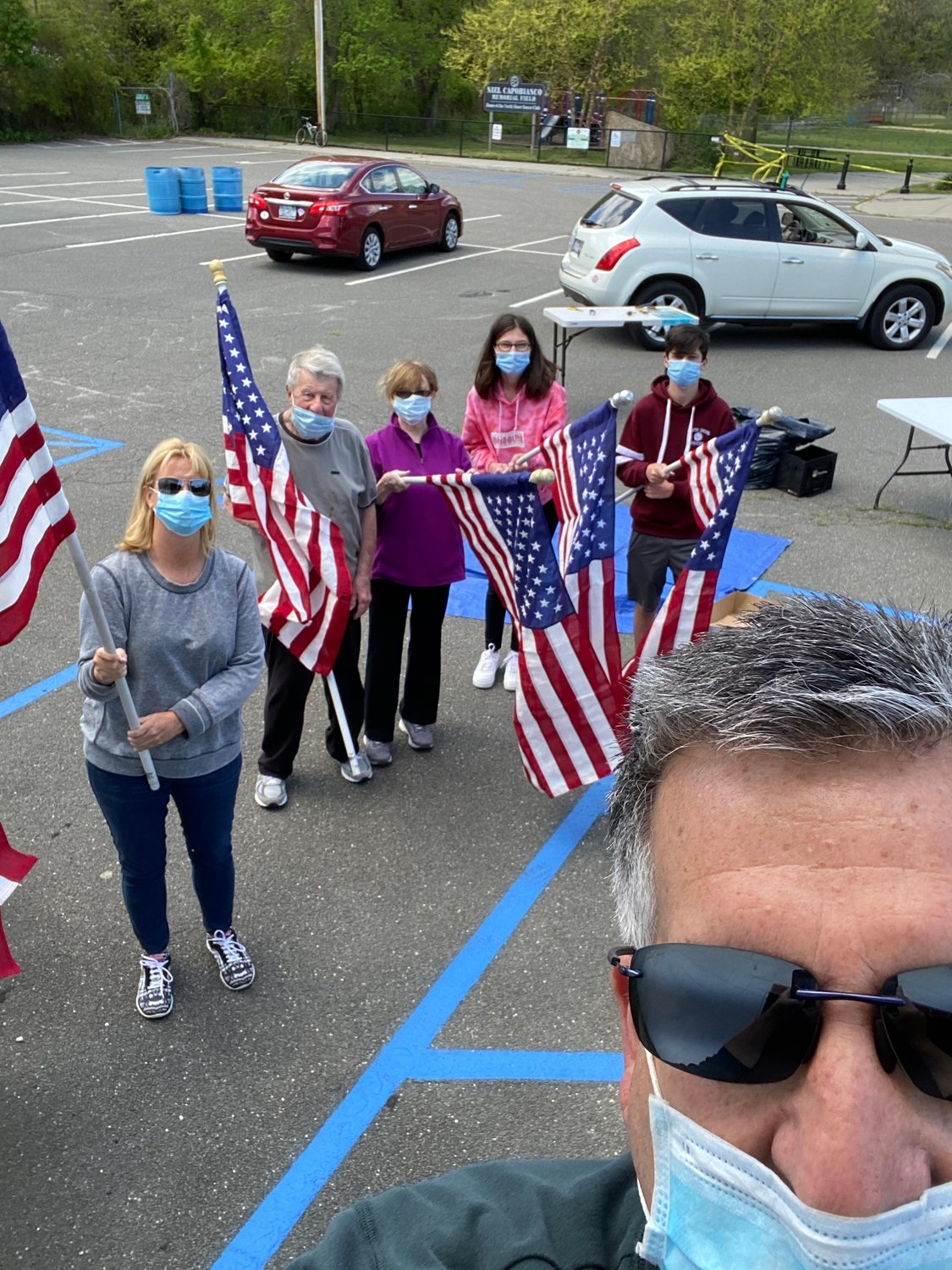 Chris Hole, foreground, joined GCBA Memorial Day Flag Chair Ronnie Thyben, above center, and, from left, Evelyn Hole, Roger Thyben, and Sofie and Brian Kraupner in hoisting flags throughout Glen Head.