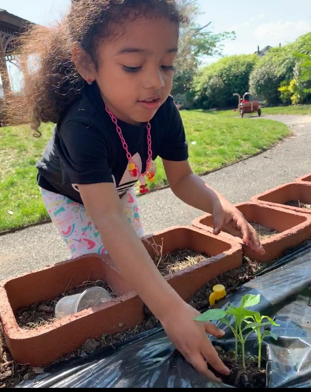 Five Towns Early Learning Center student Kasey Rosales in the school's outdoor garden.