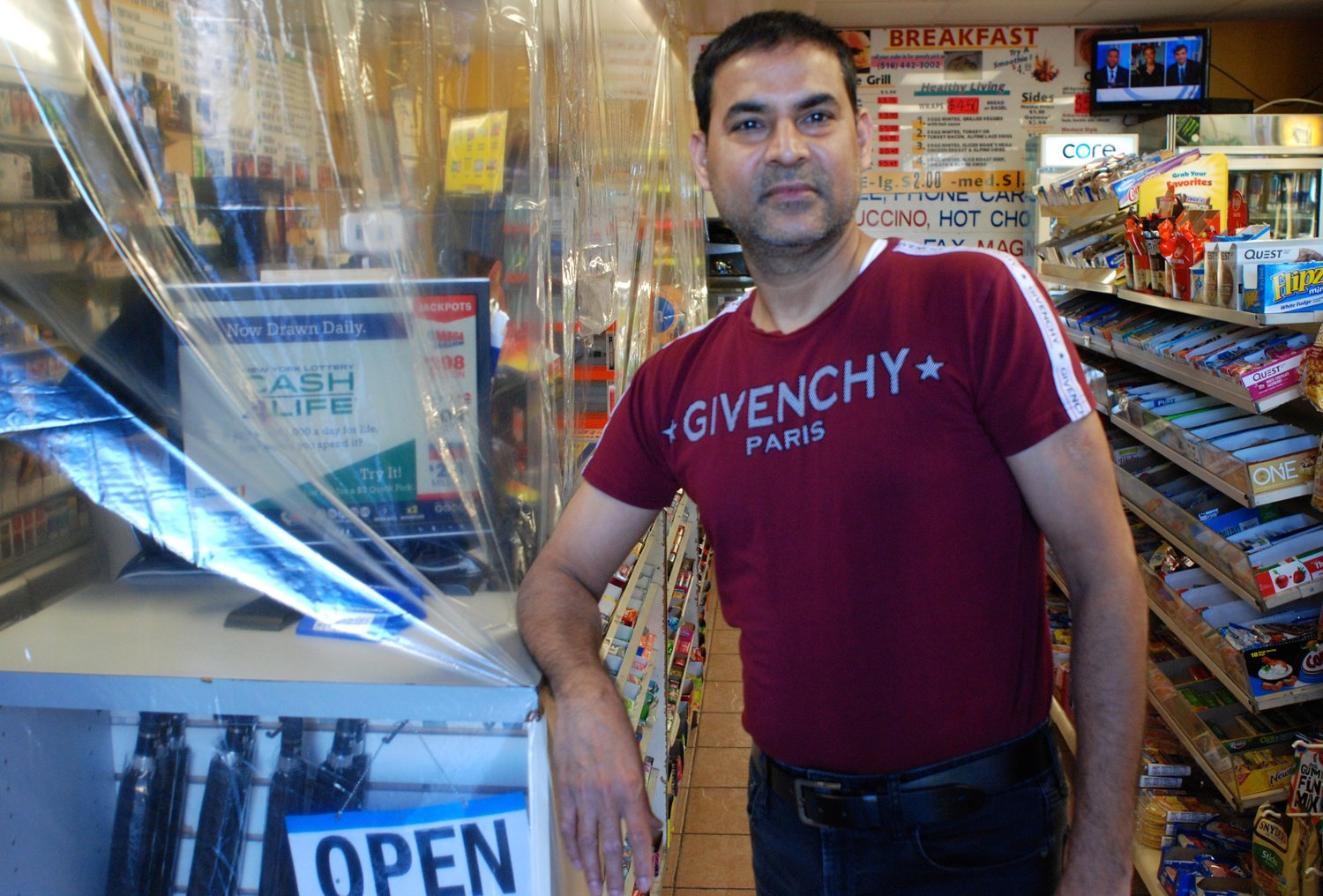 Raj Patel, of the Kaval Deli and Convenience Store, at the foot of the Rockville Centre LIRR station, with a plastic tarp around his front counter to protect himself from the virus.