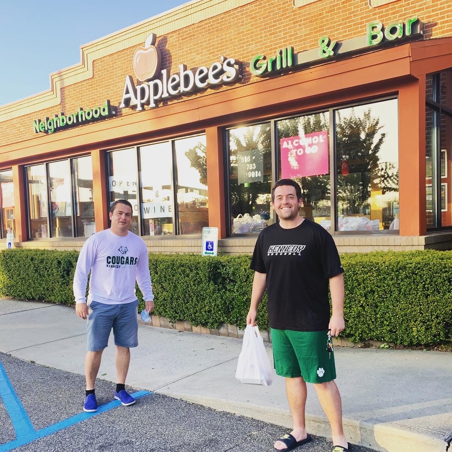 Kennedy baseball coaches Mike Gattus, left, and Ryan Cunningham, along with 25 members of the program, picked up meals at Applebee's on Thursday night.
