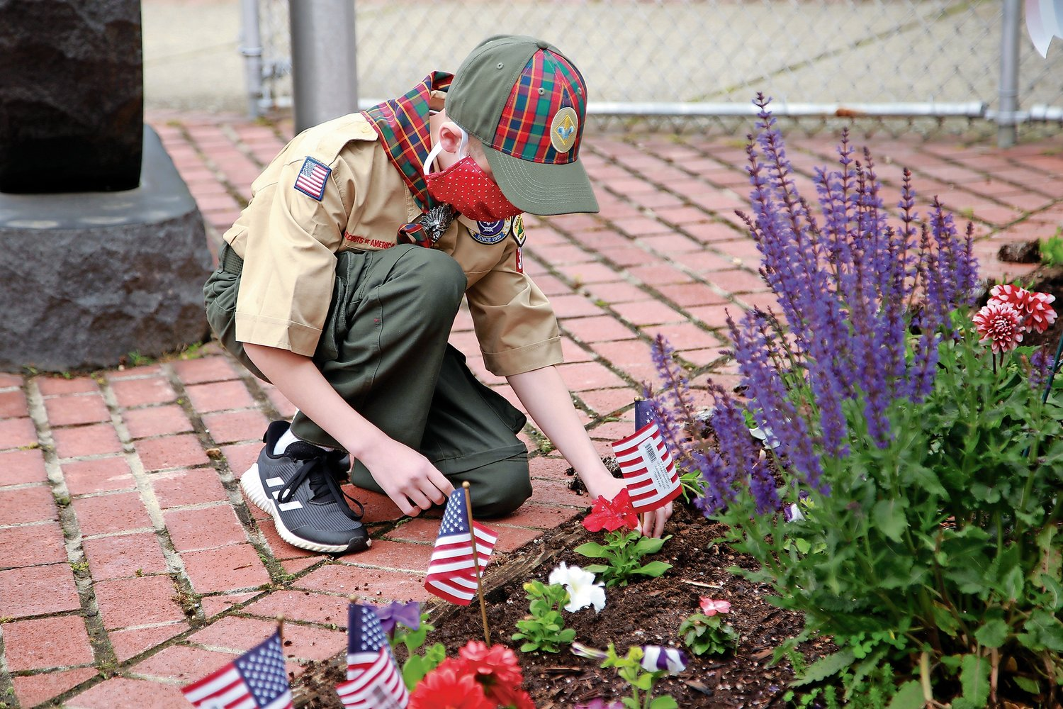 Cub Scout Vincent Ammendolea joined the rest of his pack in planting flags and flowers in the flower garden outside the VFW building in Franklin Square.