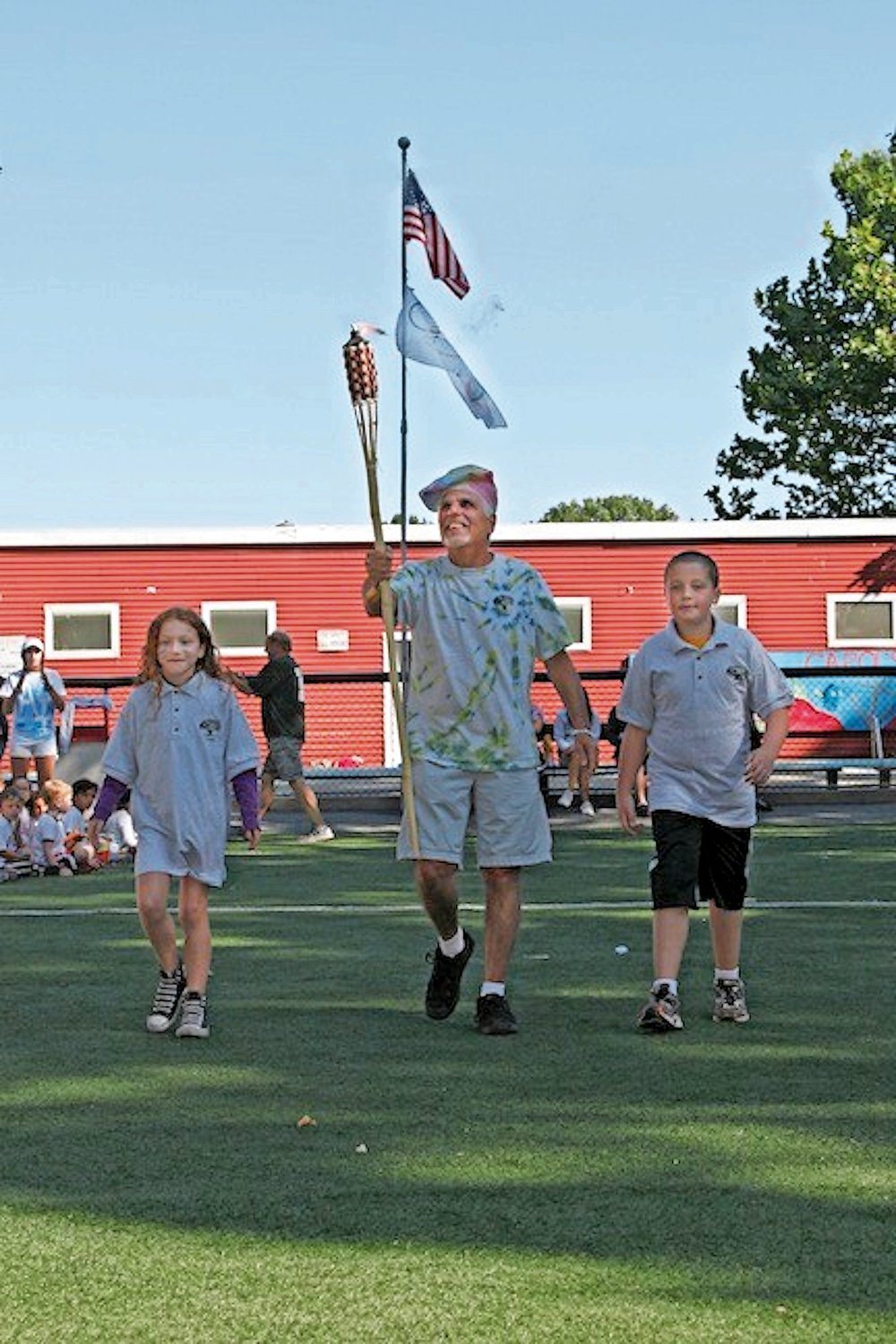 "Steve Meltzer, center, accompanied by ""camp mayors"" Haley Hepworth, 7, and Andrew Shea, 10, carried a torch at the start of Merrick Woods' Olympics-themed competition in 2013."
