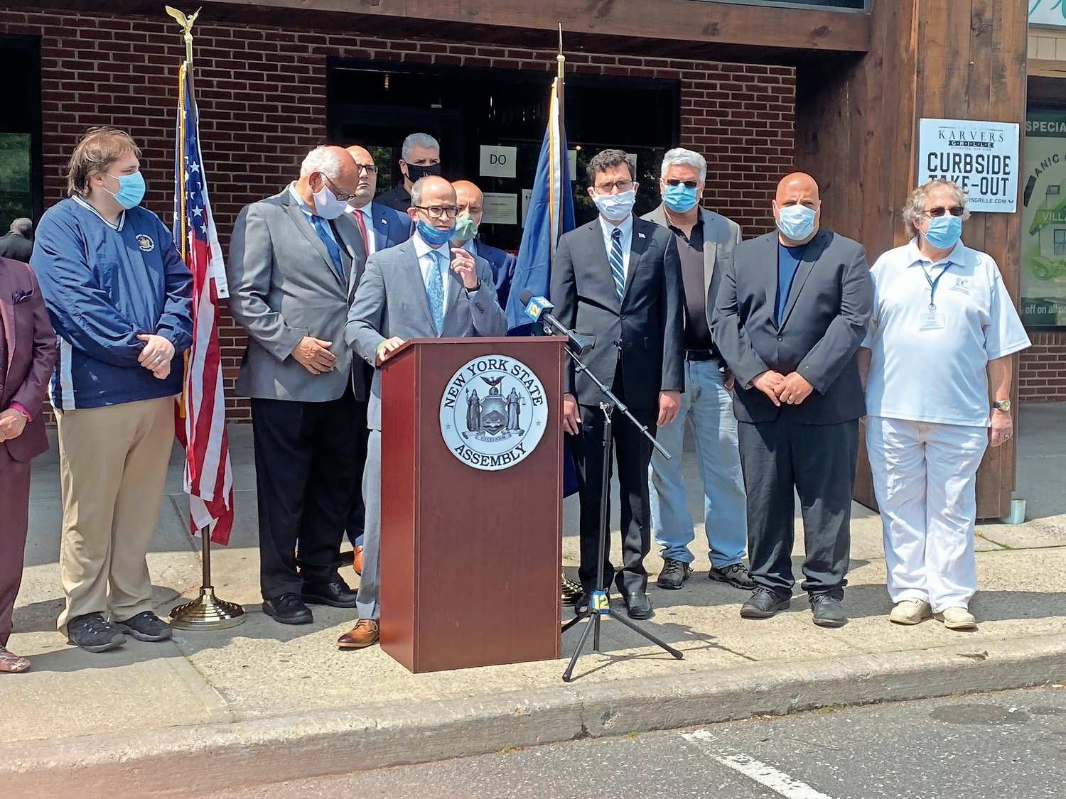 Assemblyman Ed Ra, at the lectern, proposed legislation allowing business owners to get marketing grants from the state. He spoke about it at a news conference on June 3.