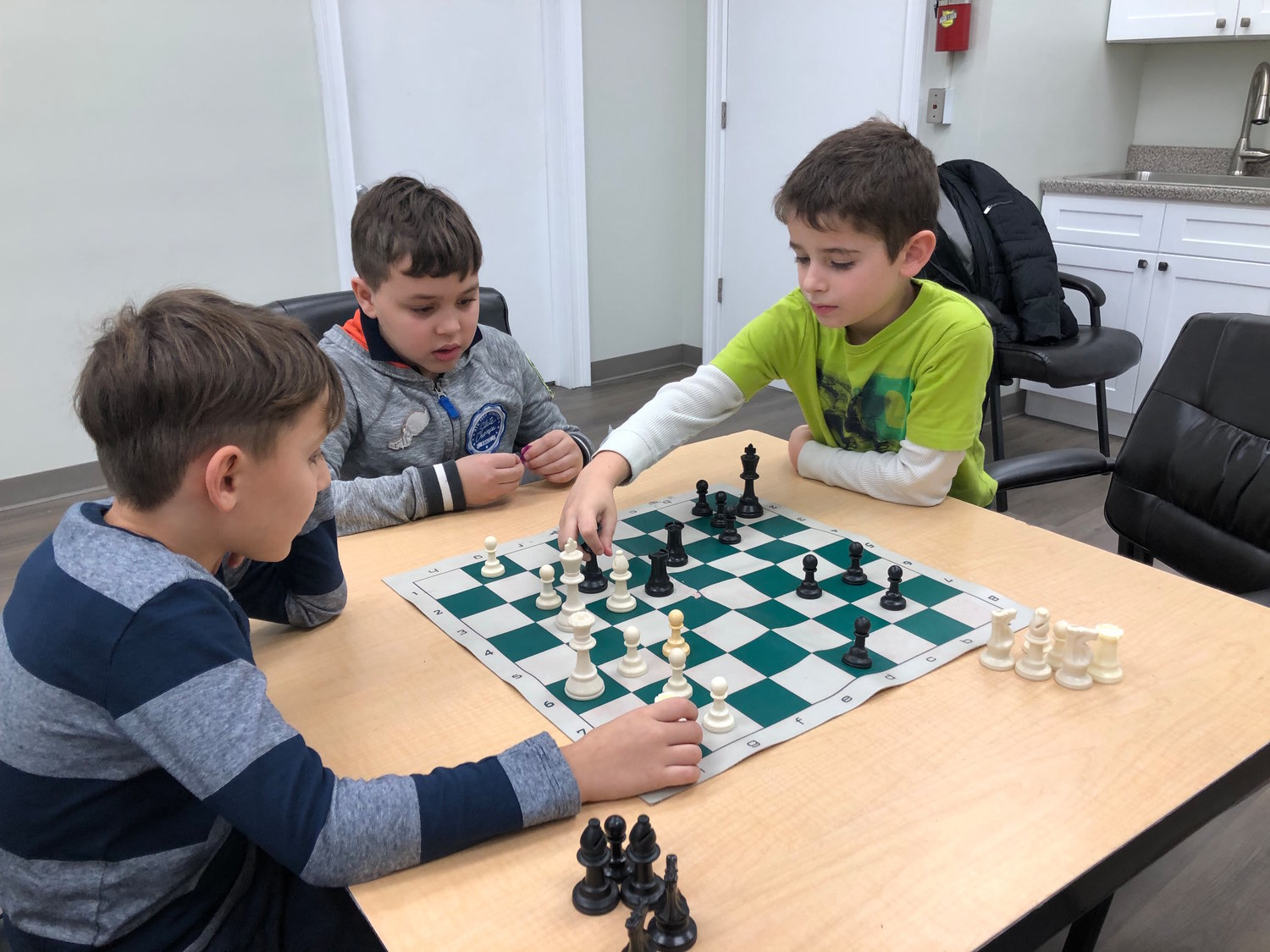 Children will have the opportunity to sign up for a virtual chess class through the Gural JCC this summer. Pictured here in December 2018 is Michael Abelev, right, making his move against Nathaniel Shamalov, left, as Marat Ustinovich oversaw the match.