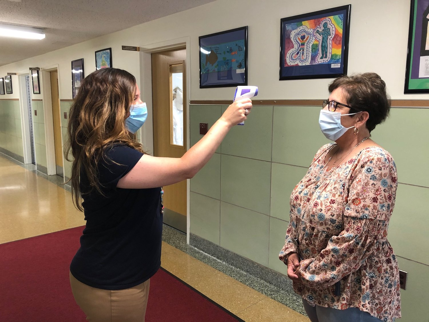 Assistant Superintendent for Curriculum and Instruction Janet Pollitt, left, demonstrated how to use an infrared thermometer on Special Education Department Secretary Kim Cavanagh.