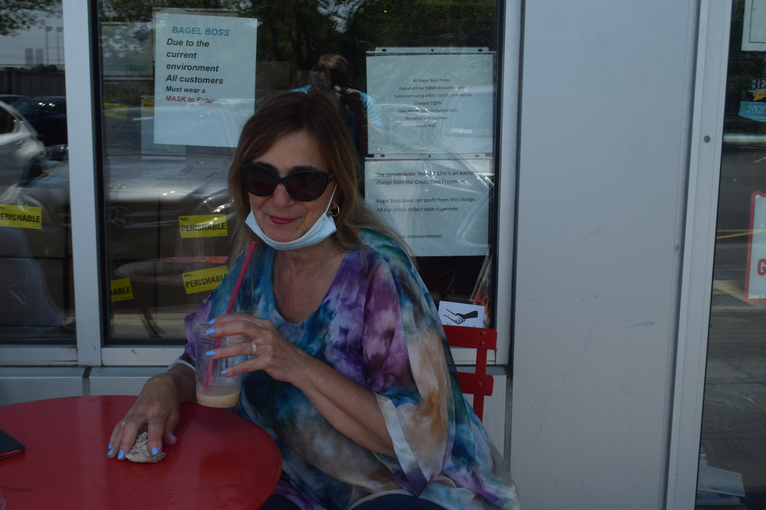 North Woodmere resident Paulina Rekatas sipped her iced coffee outside of Bagel Boss in Hewlett on the first day of Phase Two.