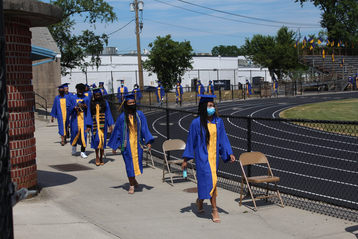 Graduates walked onto the football field.