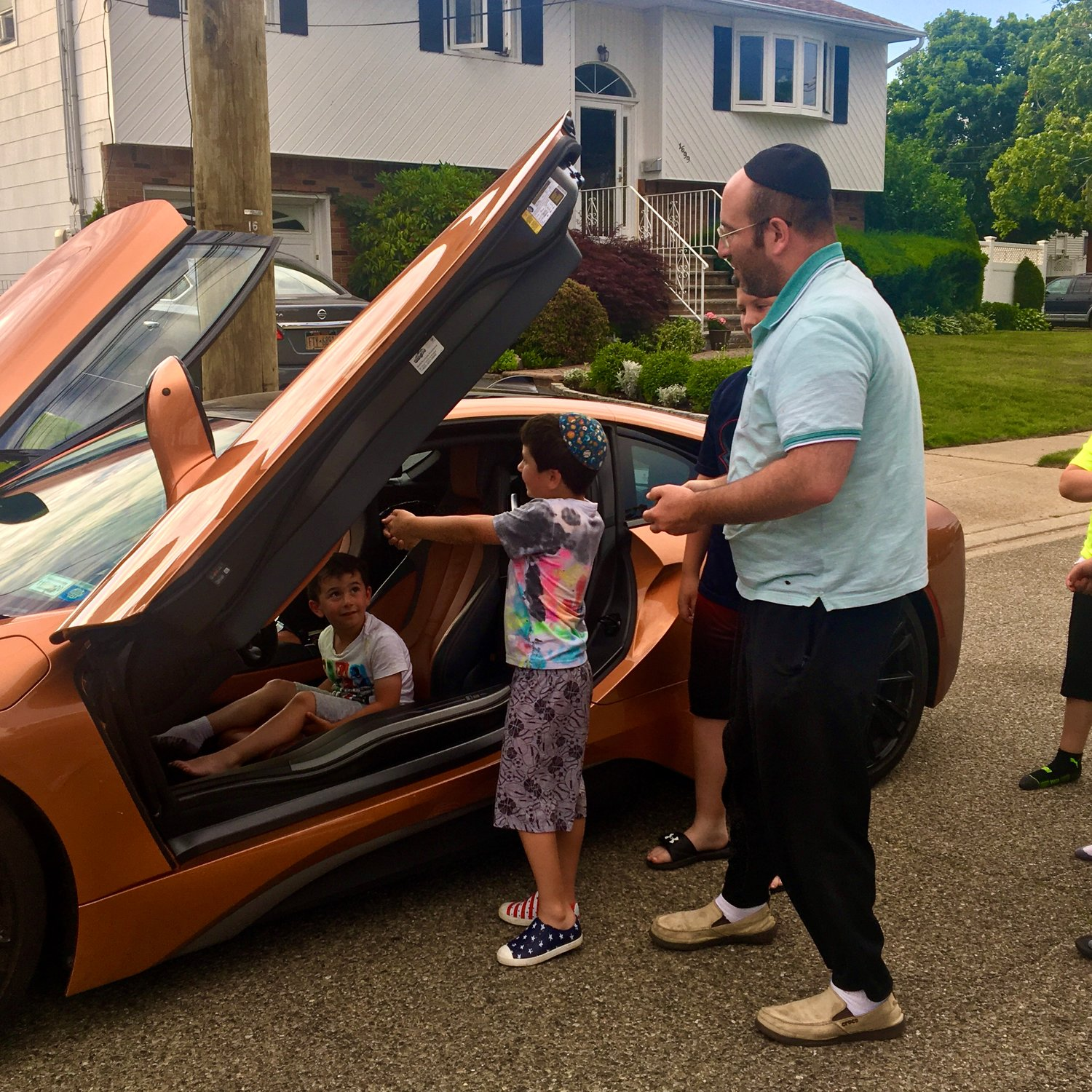 Jeremy, center, and his brother Yehuda Lieb, with their father, Yaakov Portnoy, took turns riding in a rust-colored BMW i8, a plug-in hybrid sports car.