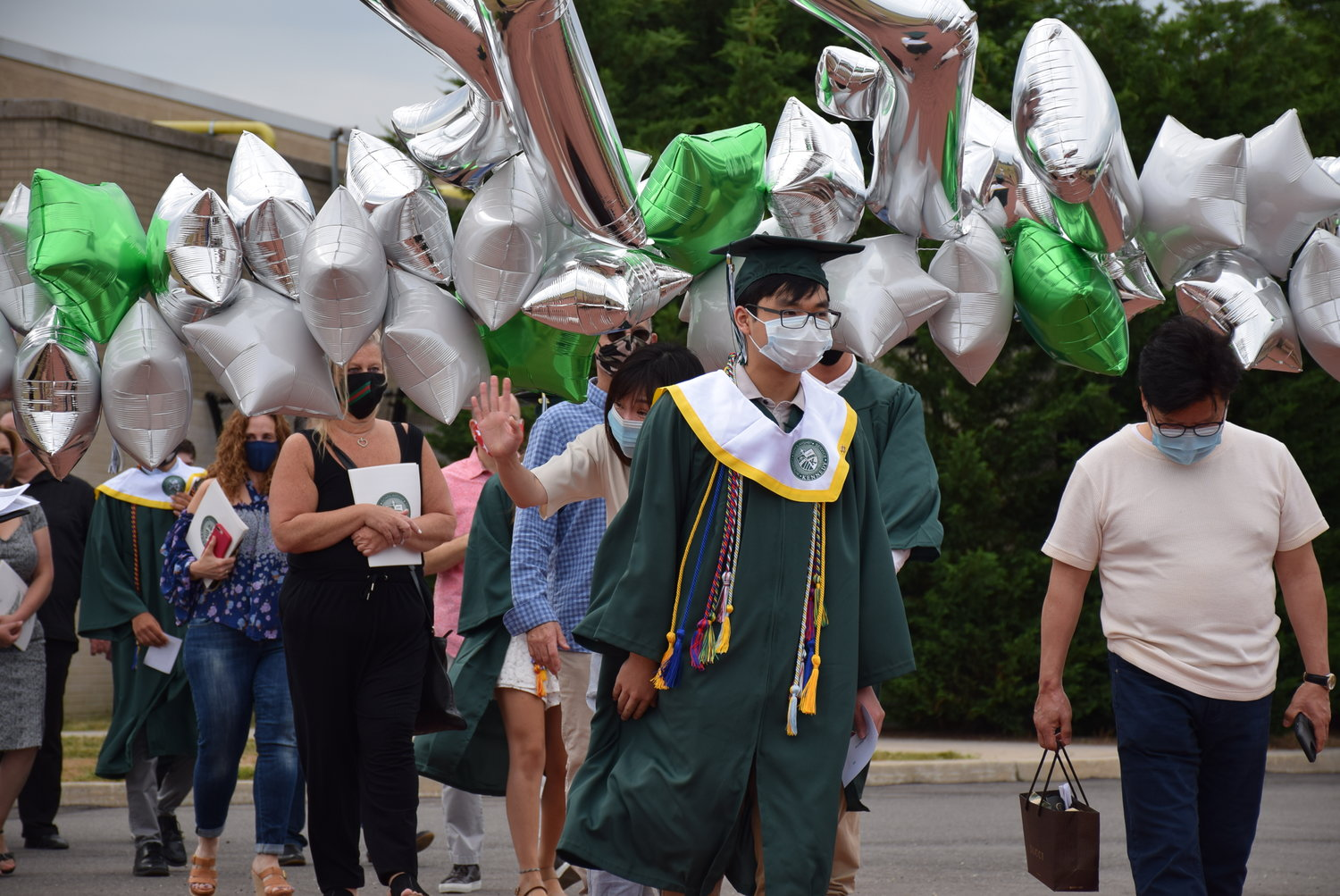 Kennedy senior Hu Cheung strolled along Cougar Walk during one of the school's graduation ceremonies on June 27.