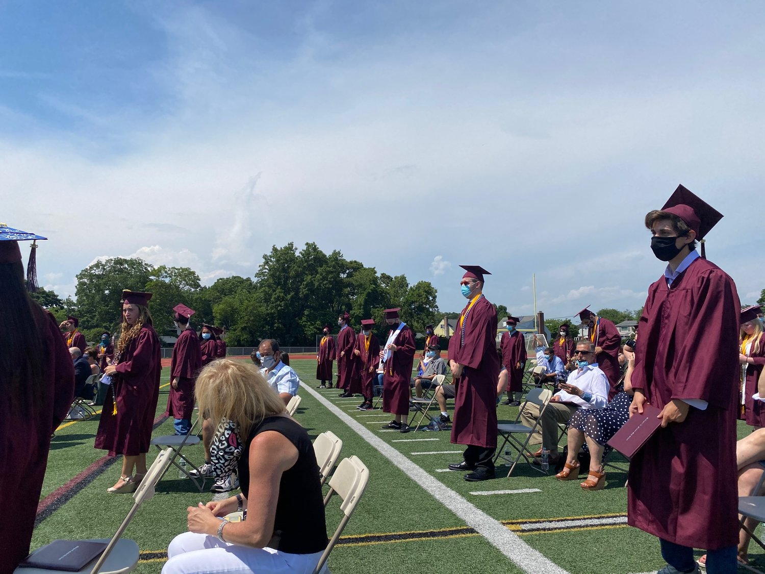 Graduates stood on the Mepham field as administrators called their names during diploma distribution.
