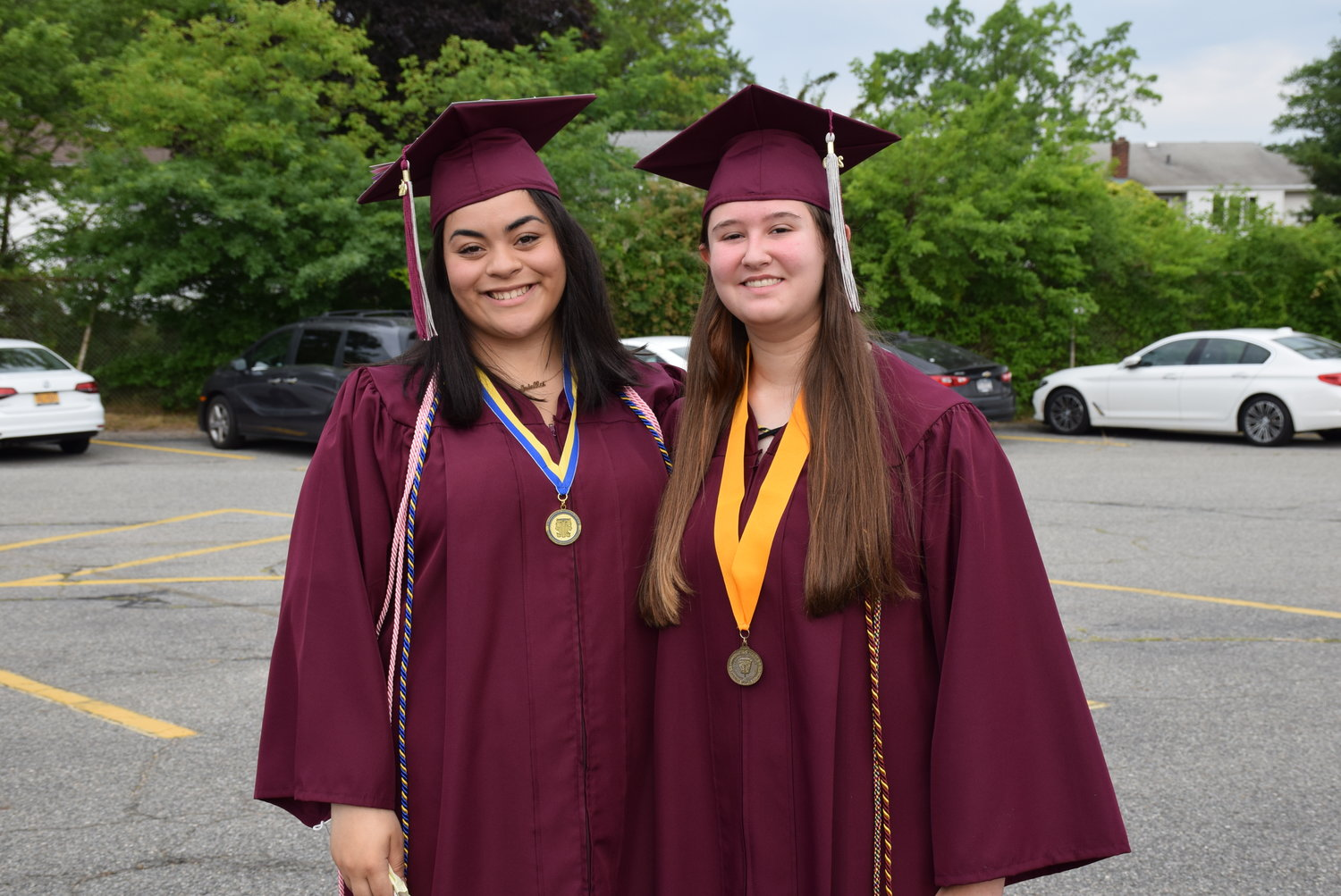 Friends Gabriella Carlotti, left, and Amanda Bremmer met in the parking lot ahead of their assigned graduation time.