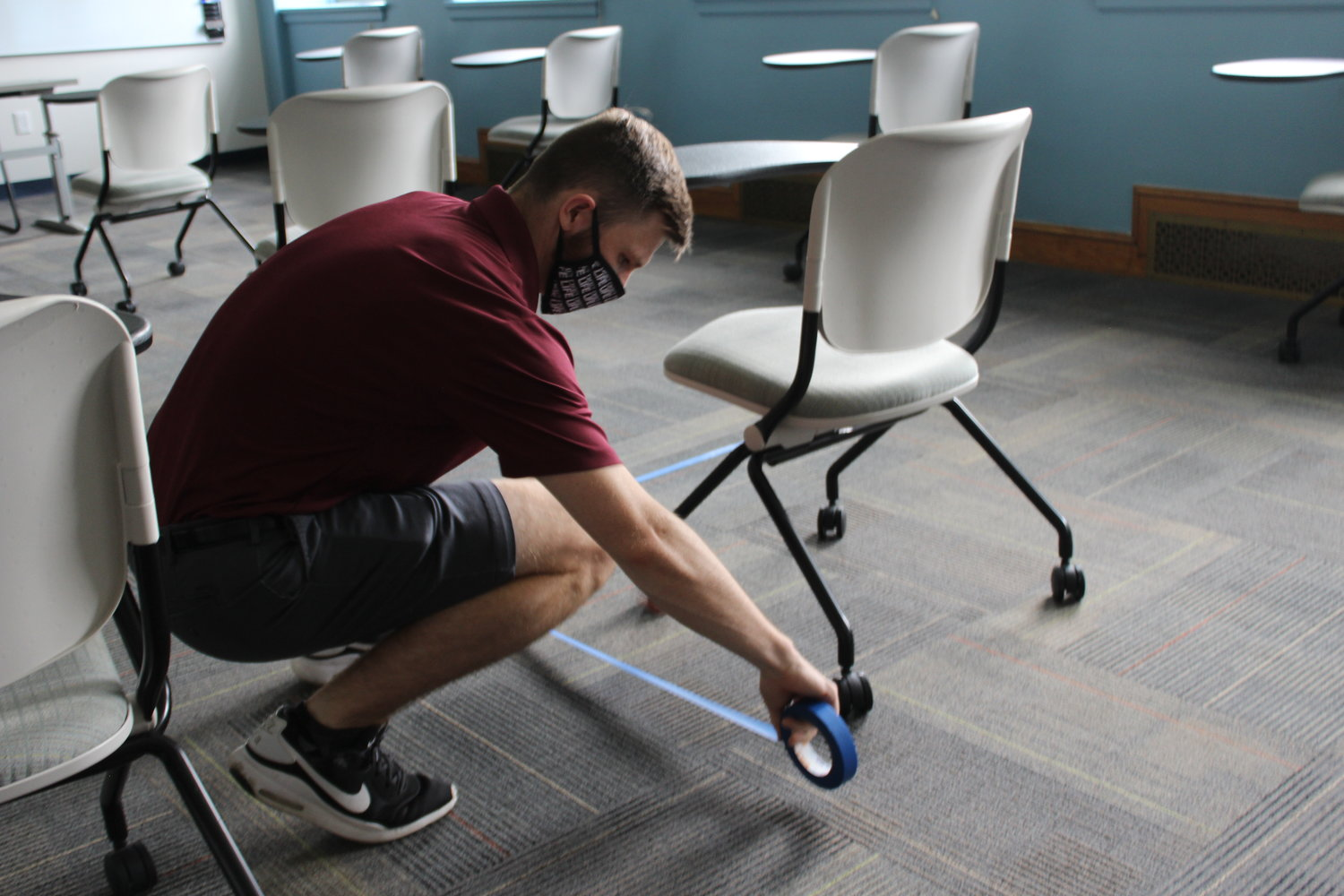 Jack Ryan, a student at Molloy, helped tape lines in a classroom to indicate where desks should be placed — each one six feet apart.