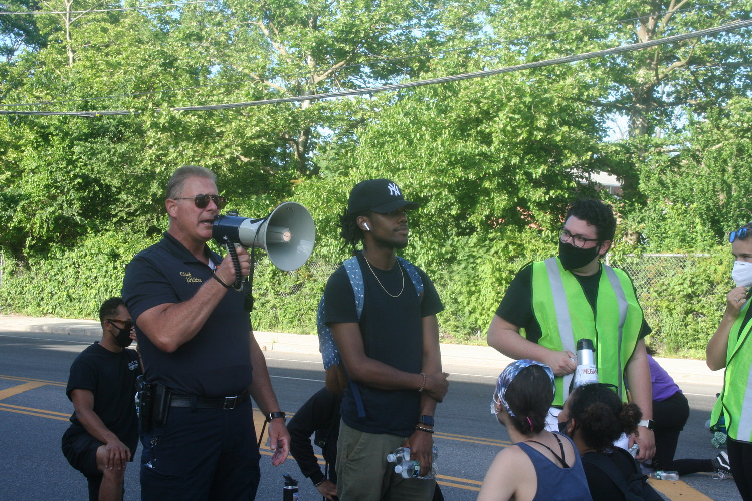 Antwan Brown, center, and protest organizer Stevens Martinez, far right, listened as Glen Cove Police Chief William Whitton told the crowd that he supported them, but would not kneel with them.