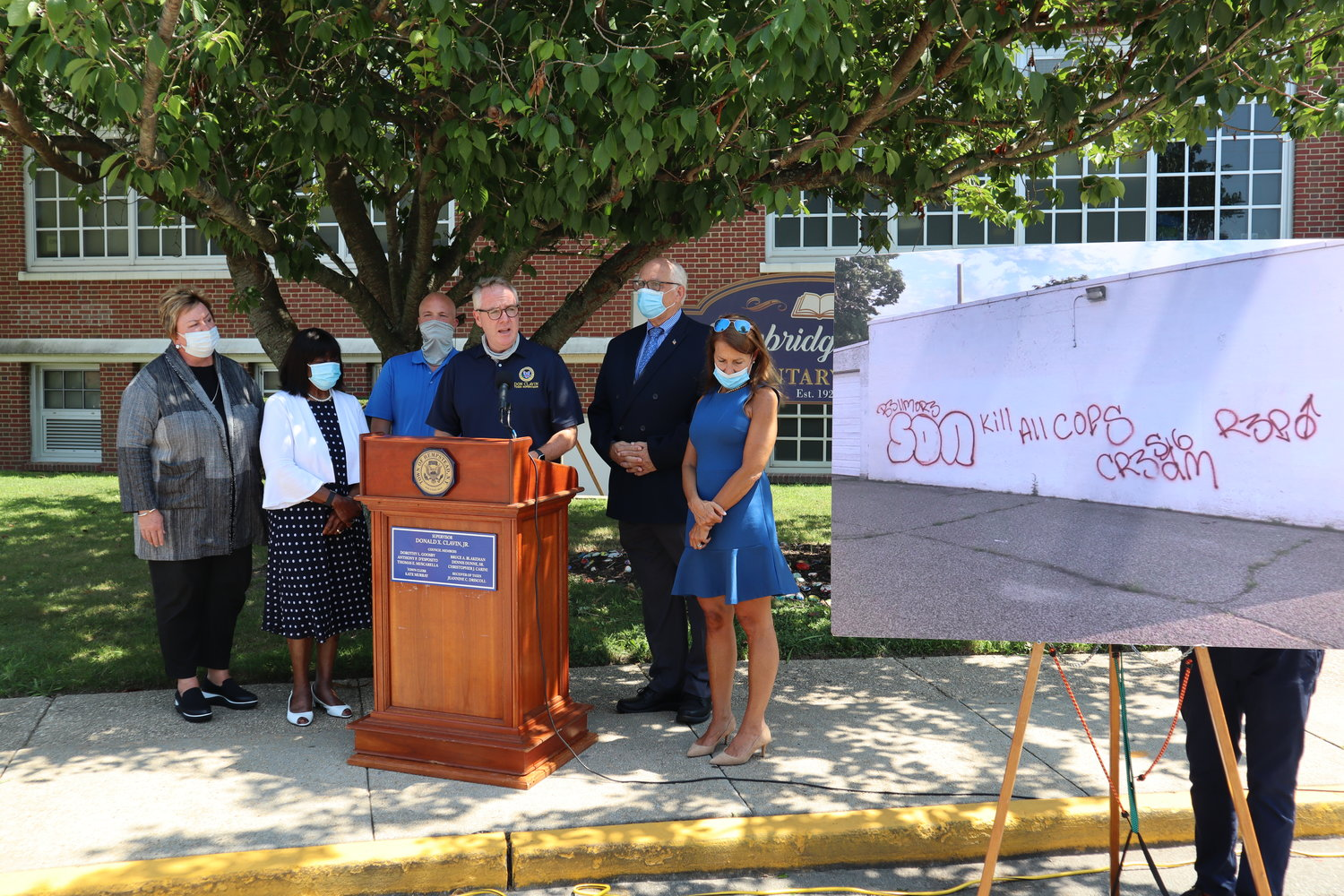 Town Board members gathered at Newbridge Road Elementary School on Monday to condemn the recent spate of graffiti. From left are District Clerk Kate Murray, Sr. Councilwoman Dorothy Goosby, Councilman Chris Carini, Supervisor Don Clavin, Councilman Dennis Dunne and Receiver of Taxes Jeanine Driscoll.