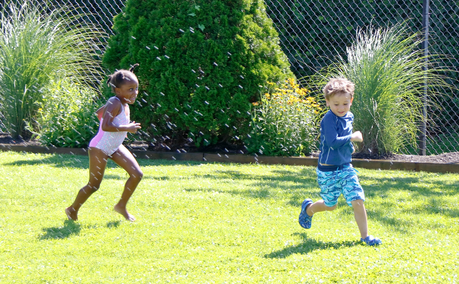 Xhara Ramsay, left, played a sprinkler-based game with Cameron Ho.