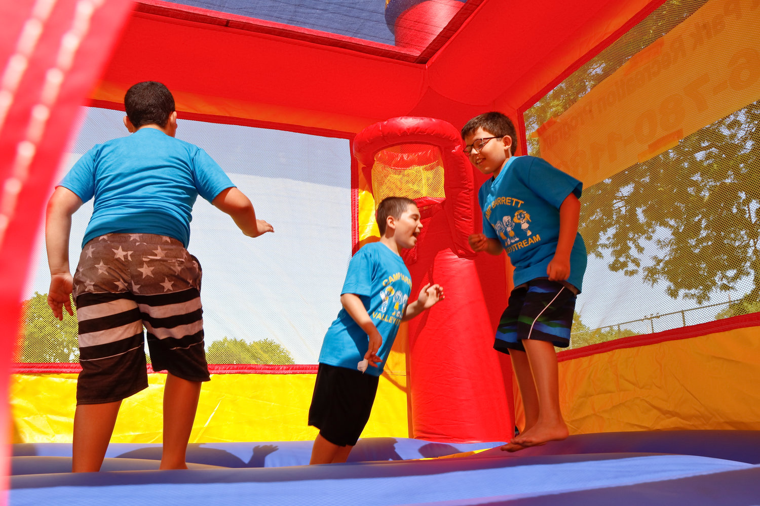 Triplets Steven, from left, Anthony and Joseph Figueroa in the camp's new bounce house.