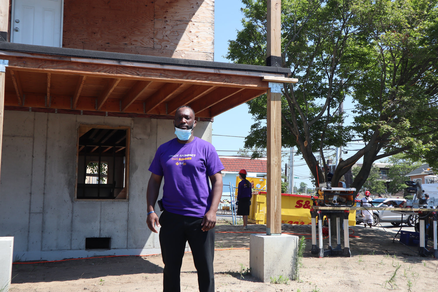 James Hodge in front of his home at Riverside Boulevard and East Fulton Street, which is being rebuilt with the help of local volunteers.