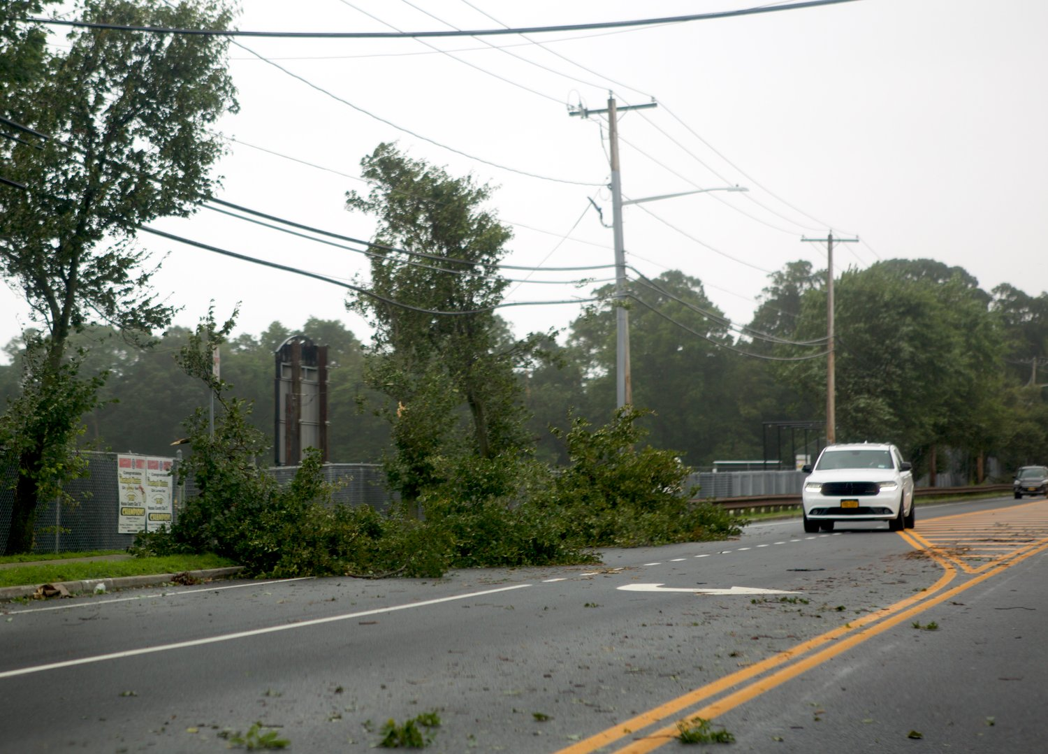 A car maneuvered past a fallen tree on Jerusalem Avenue, just north of Wantagh High School. High winds from Isiasis toppled trees across the Wantagh-Seaford area.