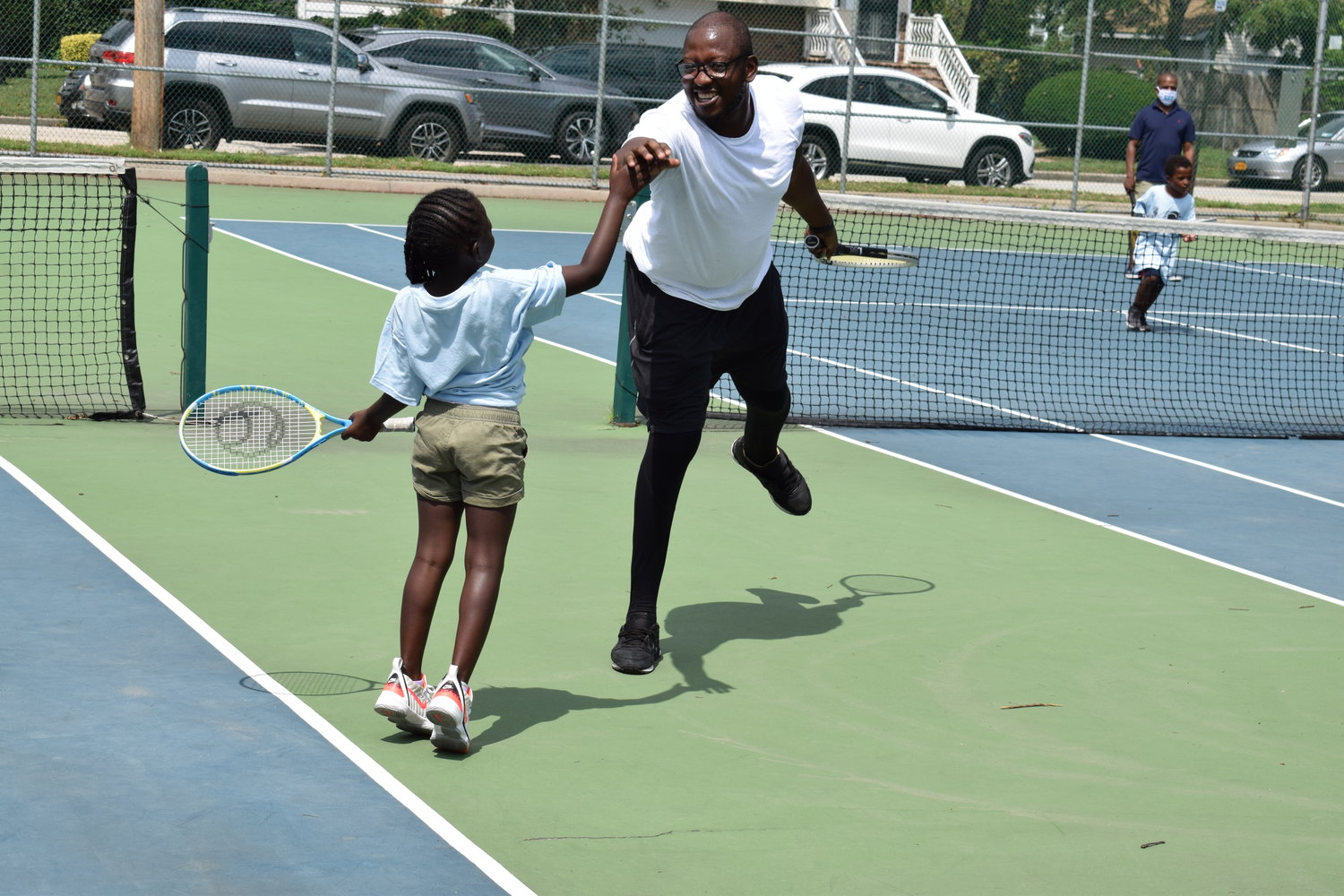 Obeng Dwamena high-fived his daughter, Aneesa Dwamena, 6, during a friendly game in the Learning Institute of Tennis, Life Skills and Sportsmanship's summer program.