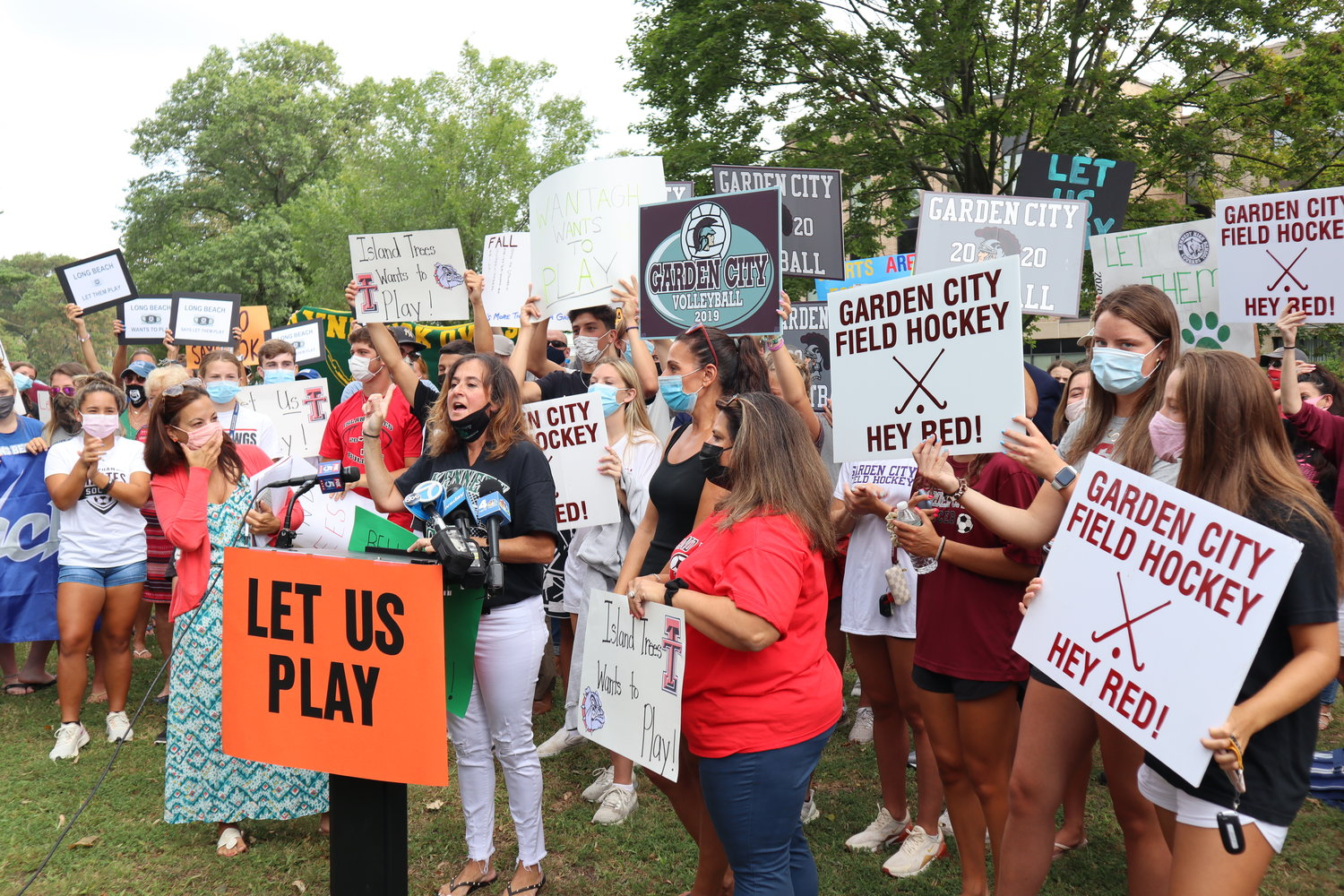 Jill Levine, at the lectern, a parent of John F. Kennedy High School athletes, helped organize a rally attended by more than 100 to call for a reversal of a decision to postpone the Nassau County sports fall season.