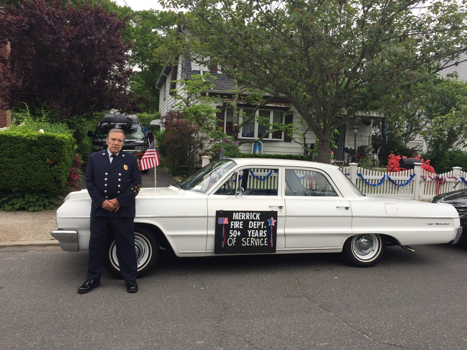 To mark his 50th year in the fire service, Martin Abrams's son chauffeured his father in Merrick's 2017 Memorial Day parade in a 1964 Chevrolet.