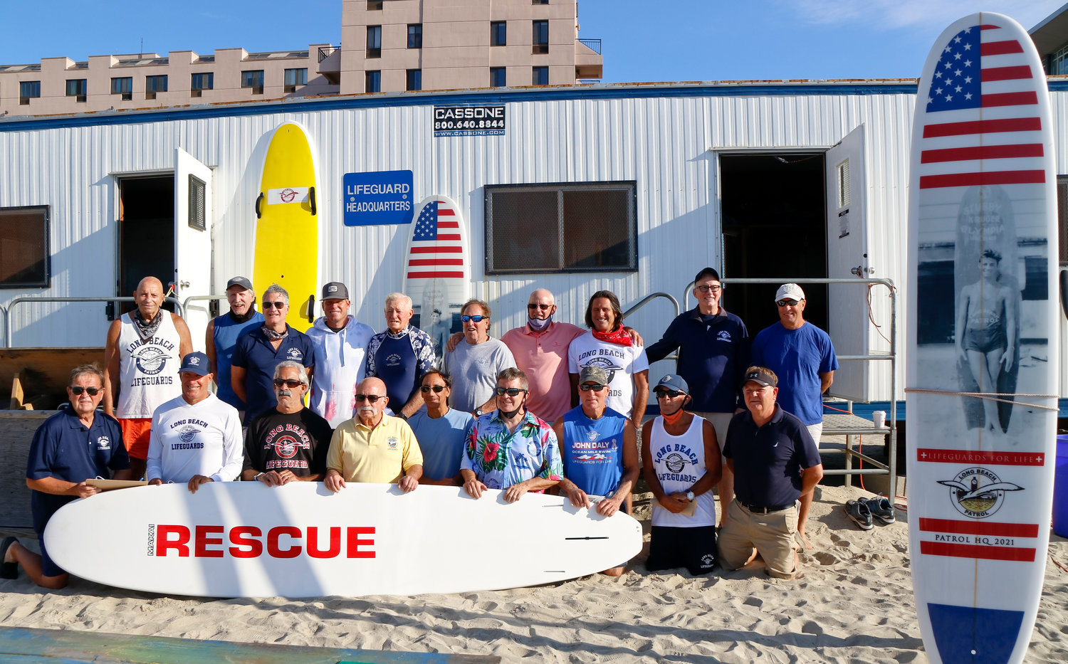The Long Beach Lifeguards Alumni Association recently raffled off a surfboard in memory of city lifeguard Richard Delury as a fundraiser. Among those at the event was Delury's brother, Mike, top row, fourth from right. Richard Delury died of natural causes in May.