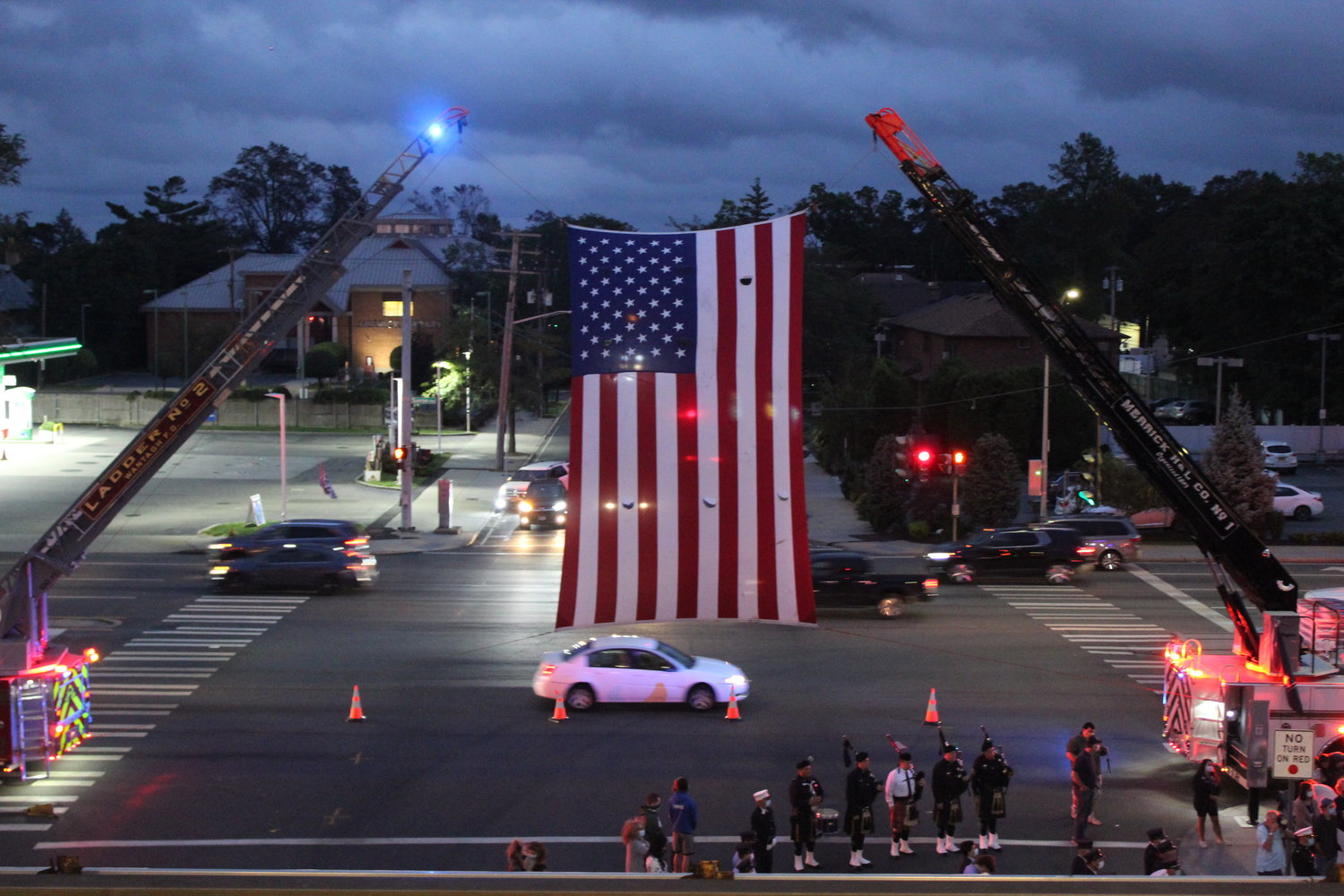 A large American flag hoisted high above the ceremony could be seen by every driver passing the intersection of Merrick Avenue and Sunrise Highway.