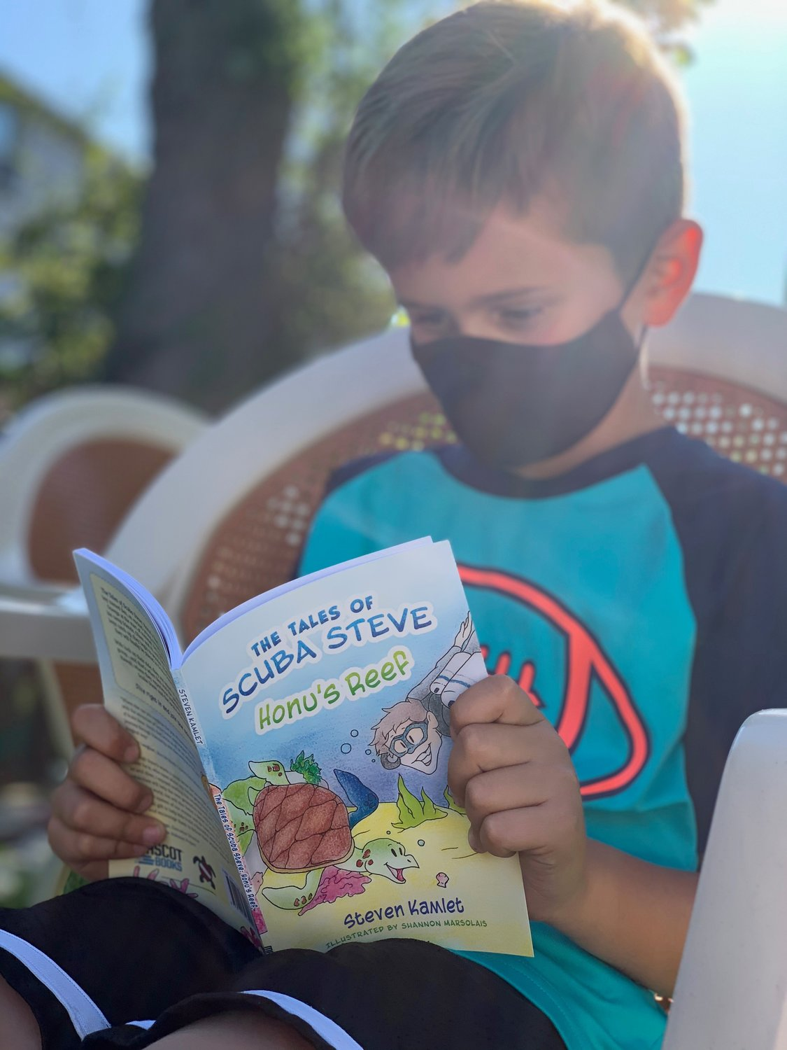 "Hunter Rogoff, of Merrick, reads ""Honu's Reef,"" the first book in ""The Tales of Scuba Steve"" series. In the book, a group of summer campers go on an undersea adventure to reconstruct Hawaii's coral reefs."