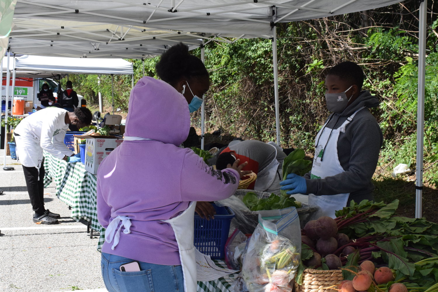 Local youths set up fresh produce at the Cedarmore Corporation's farmers market outside the Baldwin Long Island Rail Road Station on Sept. 19.